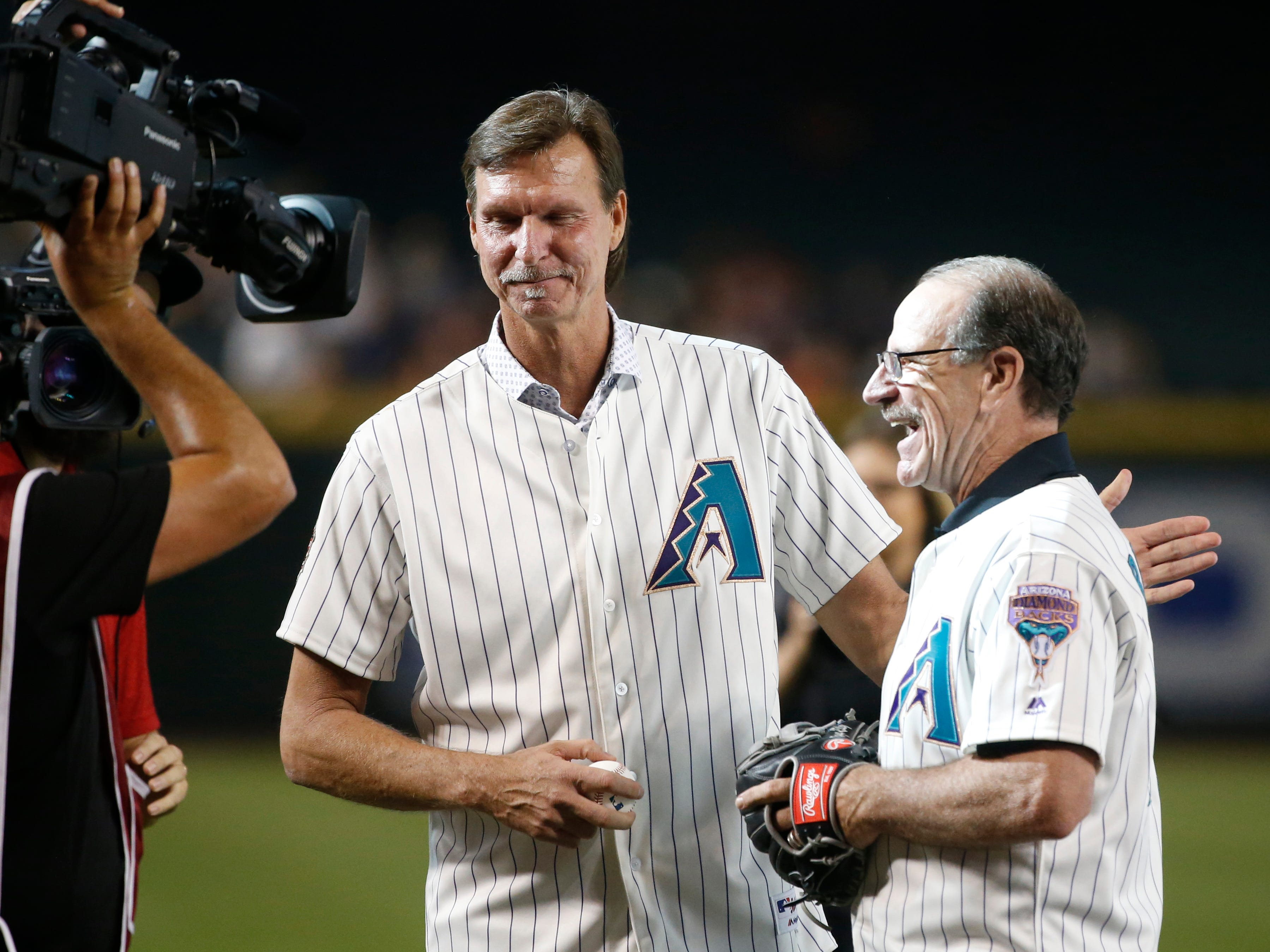 Diamondbacks Randy Johnson (L) and manager Bob Brenly greet each other after the 20th Anniversary team ceremony before a Diamondbacks game at Chase Field in Phoenix, Ariz. on Aug. 4, 2018.