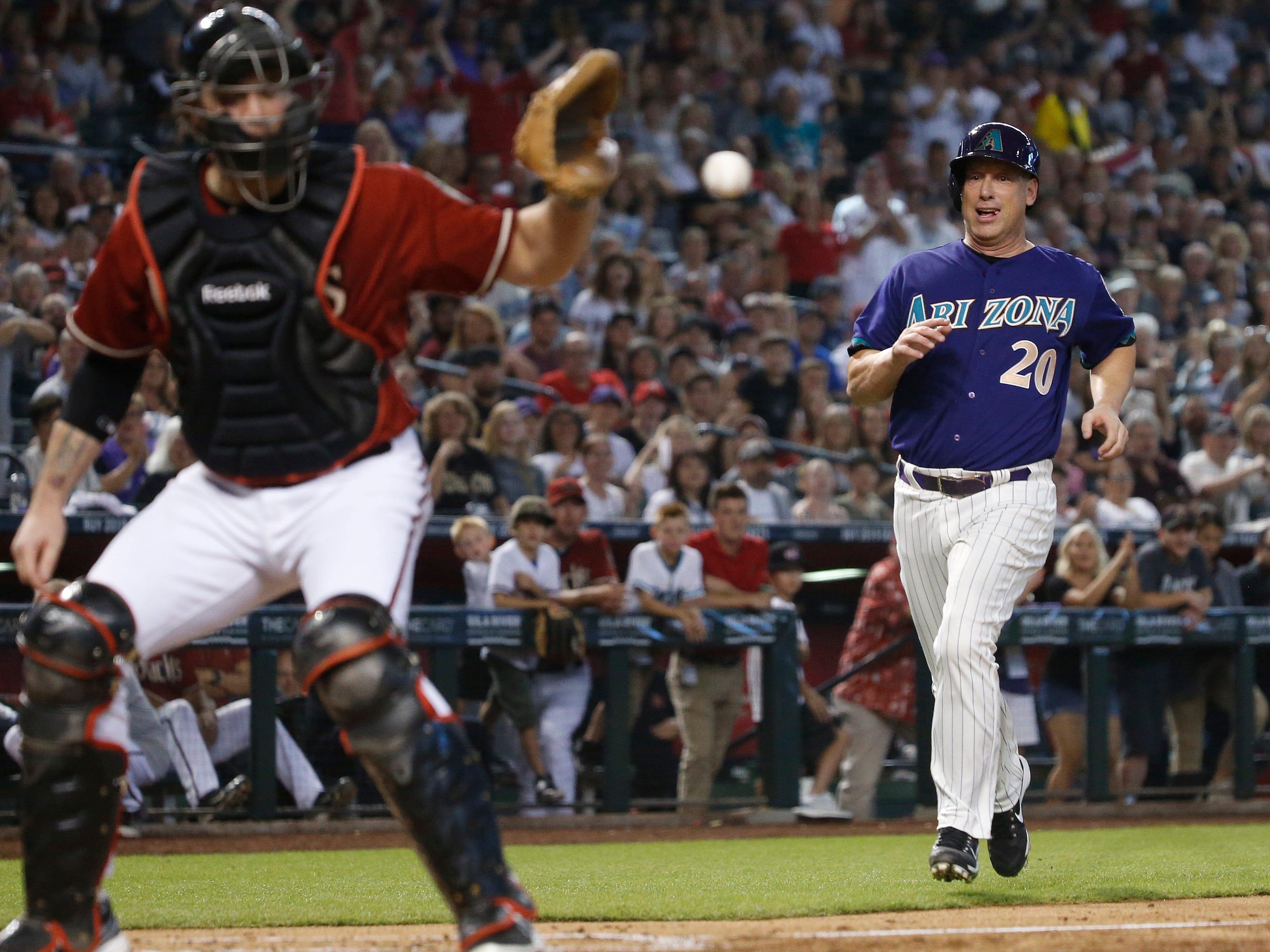 Diamondbacks Red team's Chris Snyder catches a throw at home before tagging out Purple team's Luis Gonzalez (20) during the Generations Diamondbacks Alumni game at Chase Field in Phoenix, Ariz. on Aug. 4, 2018.