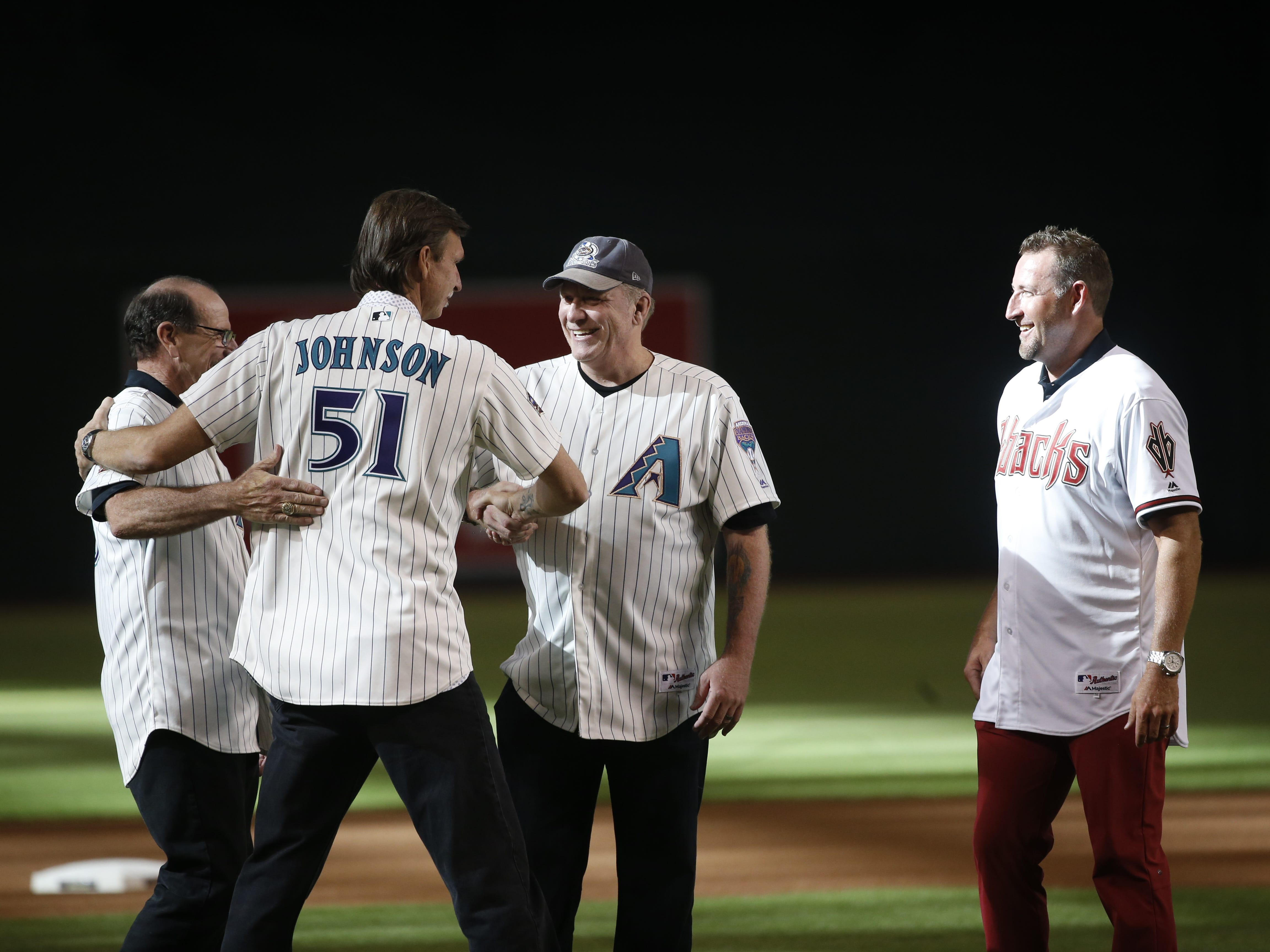 Diamondbacks Randy Johnson (51) hugs former manager Bob Brenly before greeting pitchers Curt Schilling (center) and Brandon Webb (R) as the group was chosen for the Diamondbacks 20th Anniversary team prior to a Diamondbacks game at Chase Field in Phoenix, Ariz. on Aug. 4, 2018.