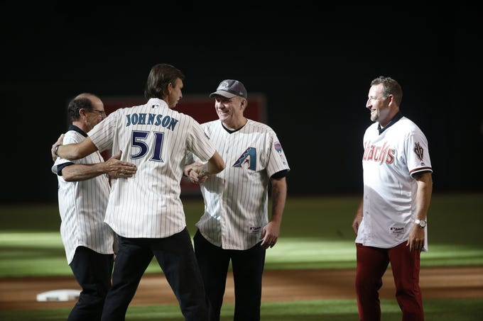 Diamondbacks Randy Johnson (51) hugs former manager Bob Brenly before greeting pitchers Curt Schilling (center) and Brandon Webb (R) as the group was chosen for the Diamondbacks 20th Anniversary team prior to a Diamondbacks game at Chase Field in Phoenix, Ariz. on Aug. 4, 2018.