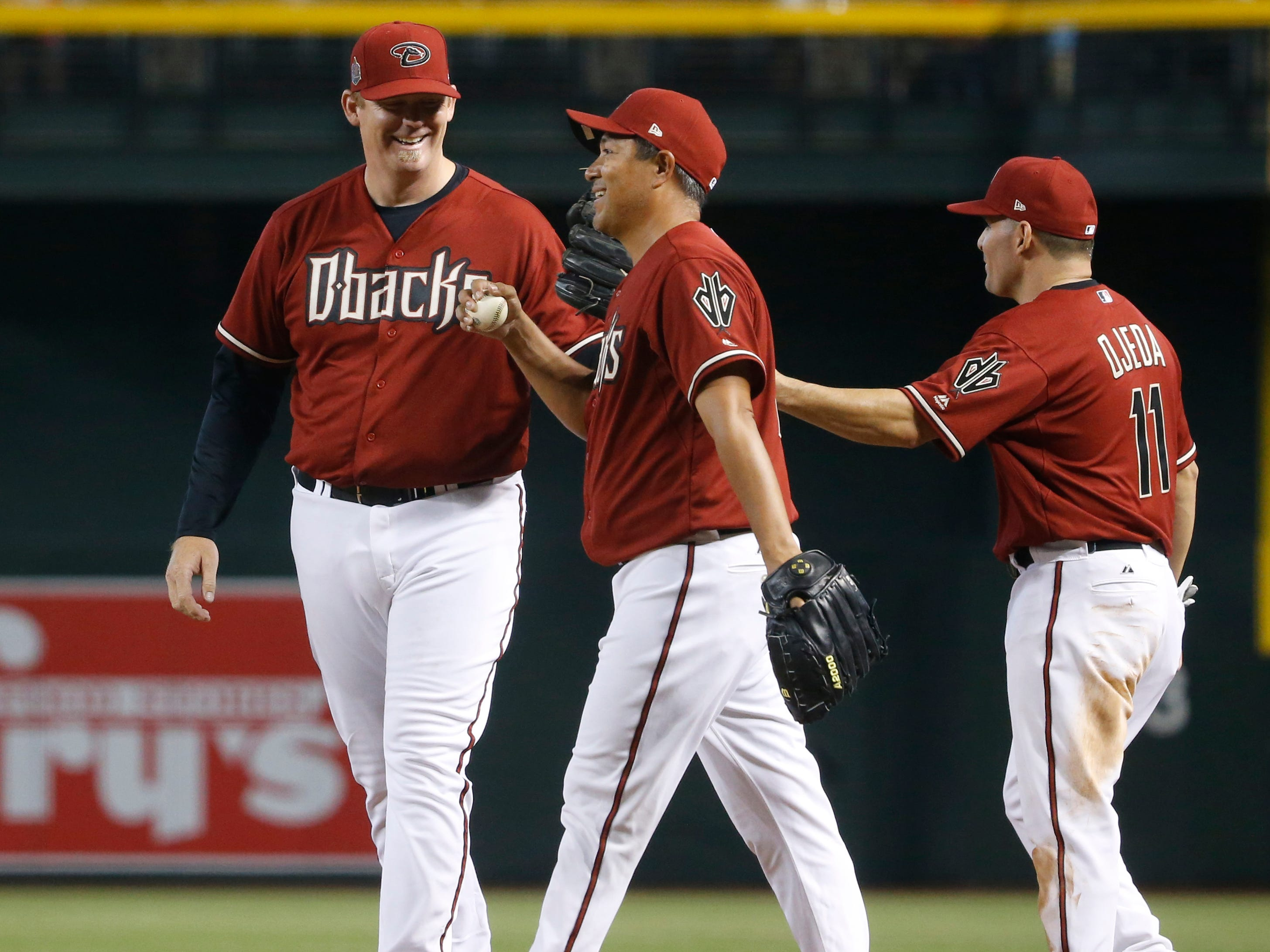 Diamondbacks Red team's Augie Ojeda (center) laughs with JJ Putz (L) after the two can't complete an out at first during the Generations Diamondbacks Alumni game at Chase Field in Phoenix, Ariz. on Aug. 4, 2018.