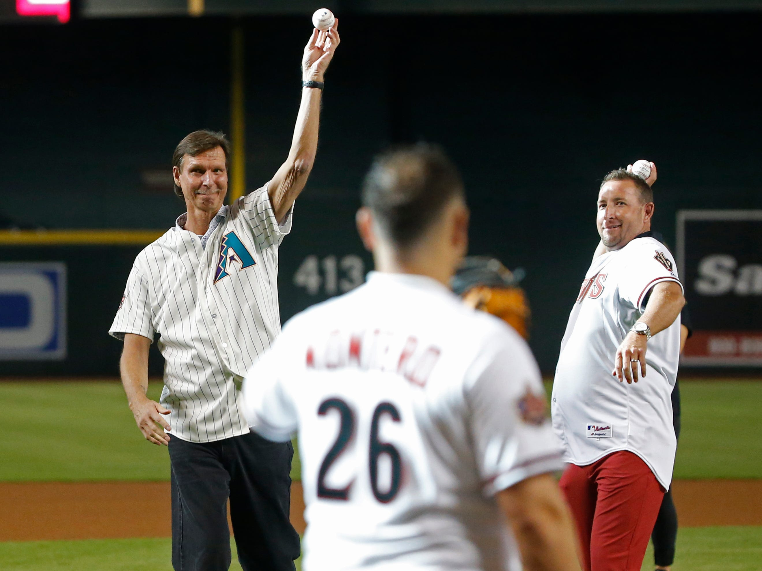Diamondbacks Randy Johnson (L) and Brandon Webb throw out the first pitch with their teammates of the 20th Anniversary team before a Diamondbacks game at Chase Field in Phoenix, Ariz. on Aug. 4, 2018.