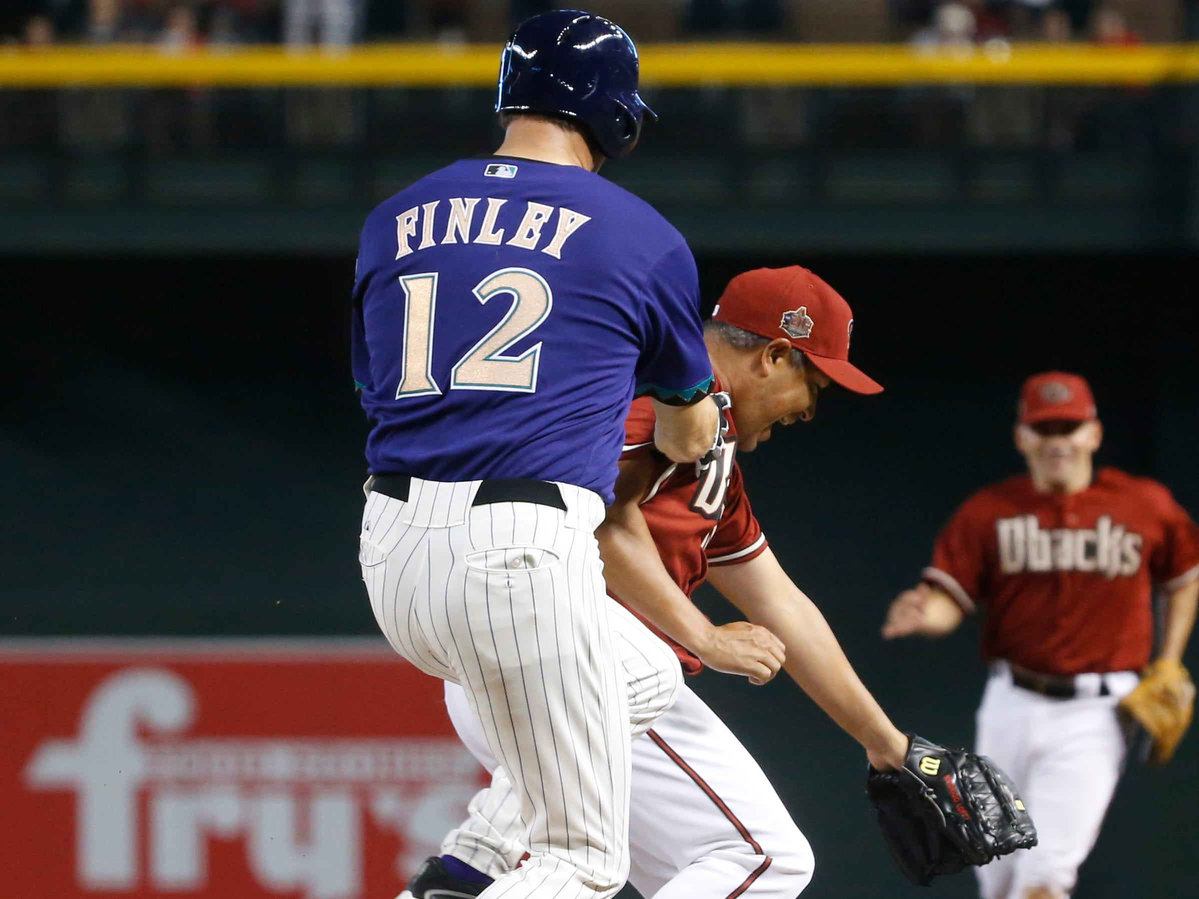 Diamondbacks Purple team's Steve Finley (12) runs into the back of Red team's Augie Ojeda during the Generations Diamondbacks Alumni game at Chase Field in Phoenix, Ariz. on Aug. 4, 2018.