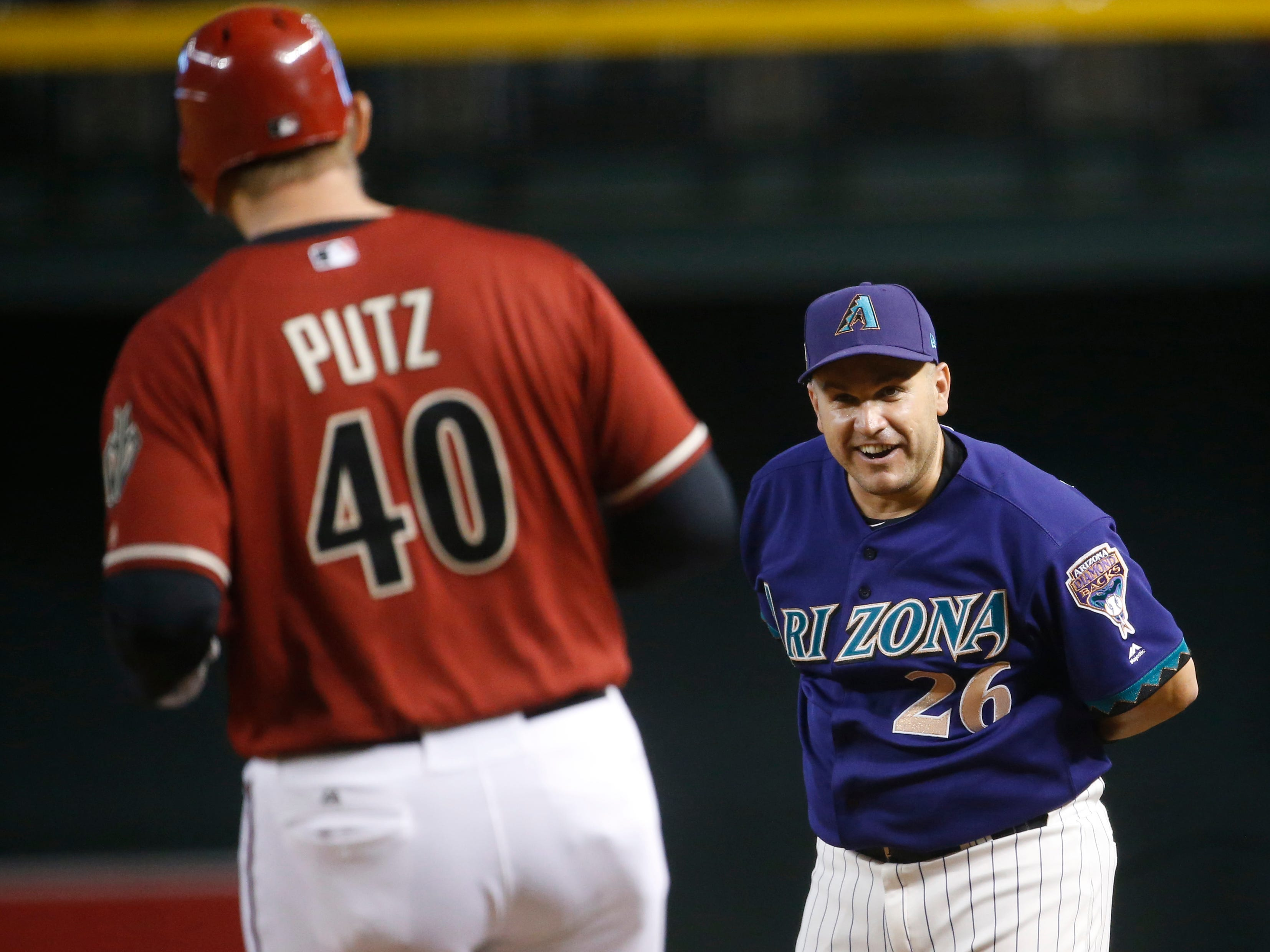 Diamondbacks Purple team's Miguel Montero (26) jokes with Red team's JJ Putz after Putz singles in his at bat against the Purple team during the Generations Diamondbacks Alumni game at Chase Field in Phoenix, Ariz. on Aug. 4, 2018.
