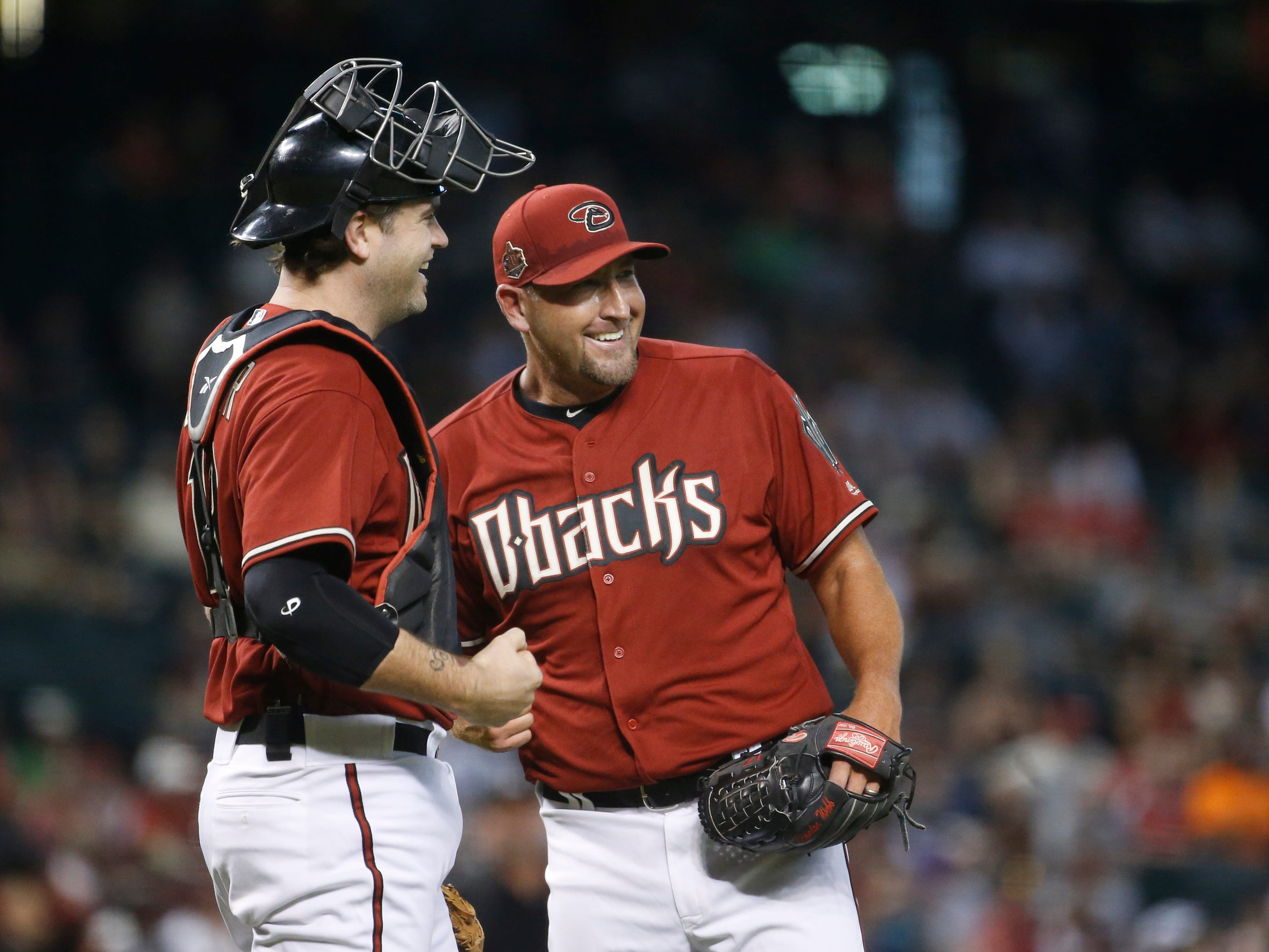 Diamondbacks Red team's Brandon Webb high-fives catcher Chris Snyder (19) after being pulled in the first inning during the Generations Diamondbacks Alumni game at Chase Field in Phoenix, Ariz. on Aug. 4, 2018.