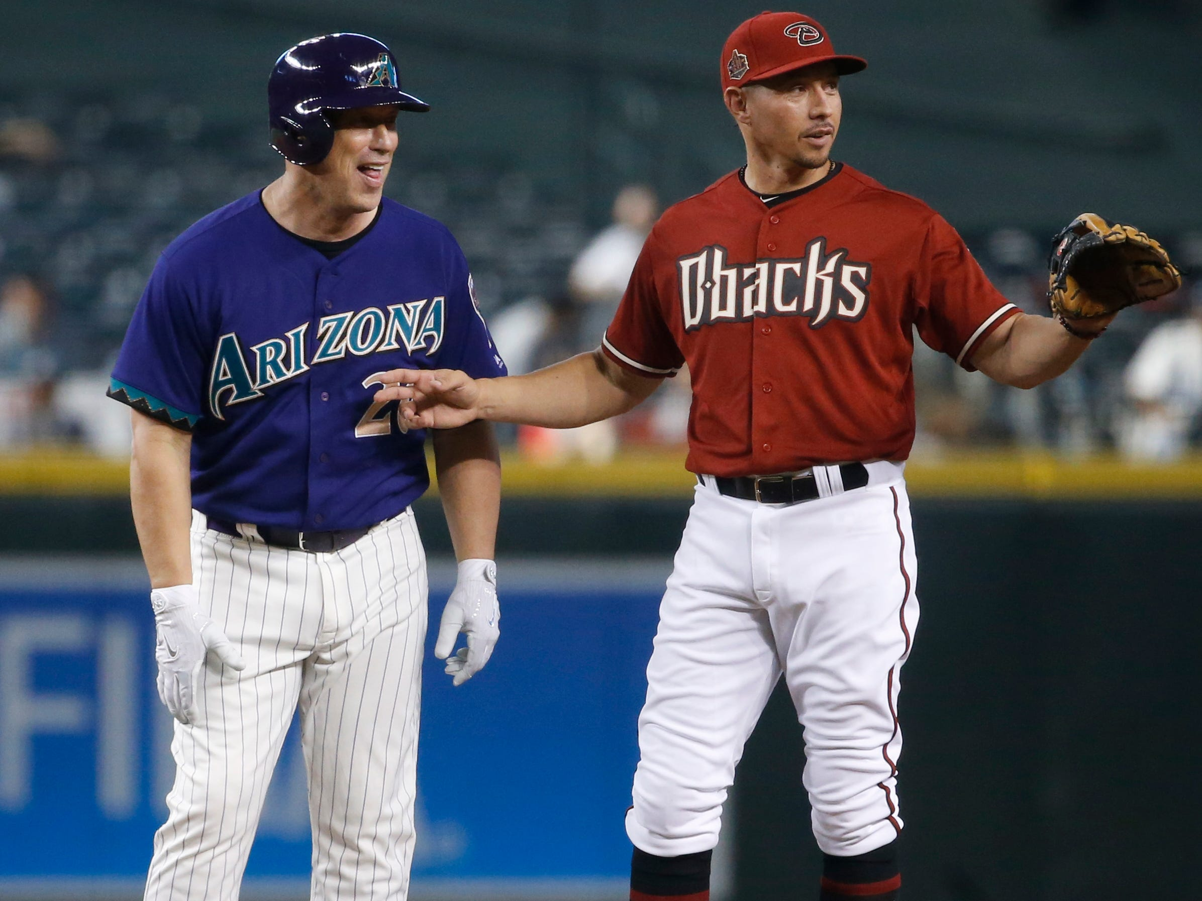 Diamondbacks Purple team's Luis Gonzalez (20) winds up at second after a hit against the Red team during the Generations Diamondbacks Alumni game at Chase Field in Phoenix, Ariz. on Aug. 4, 2018.
