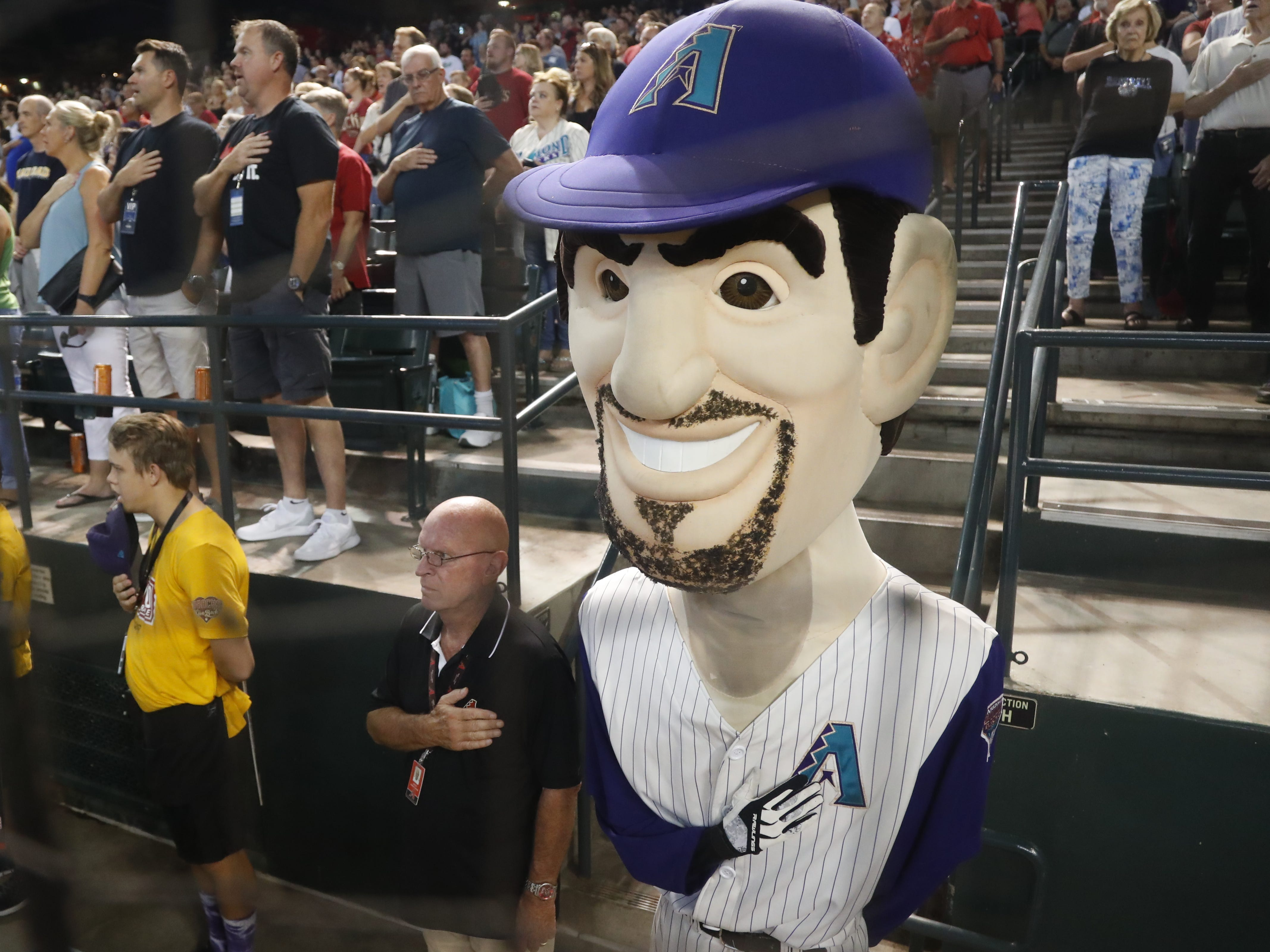 A Luis Gonzalez mascot holds his hand over his heart prior to the Generations Diamondbacks Alumni game at Chase Field in Phoenix, Ariz. on Aug. 4, 2018.