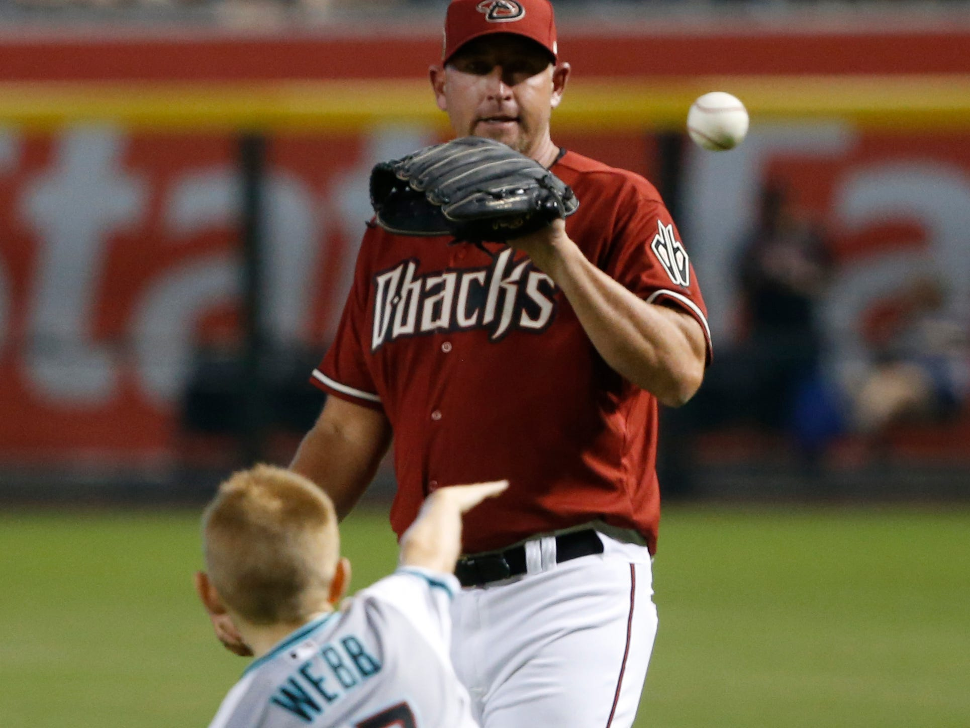 Diamondbacks Red team pitcher Brandon Webb throws the ball with his son as he warms up for the Generations Diamondbacks Alumni game at Chase Field in Phoenix, Ariz. on Aug. 4, 2018.