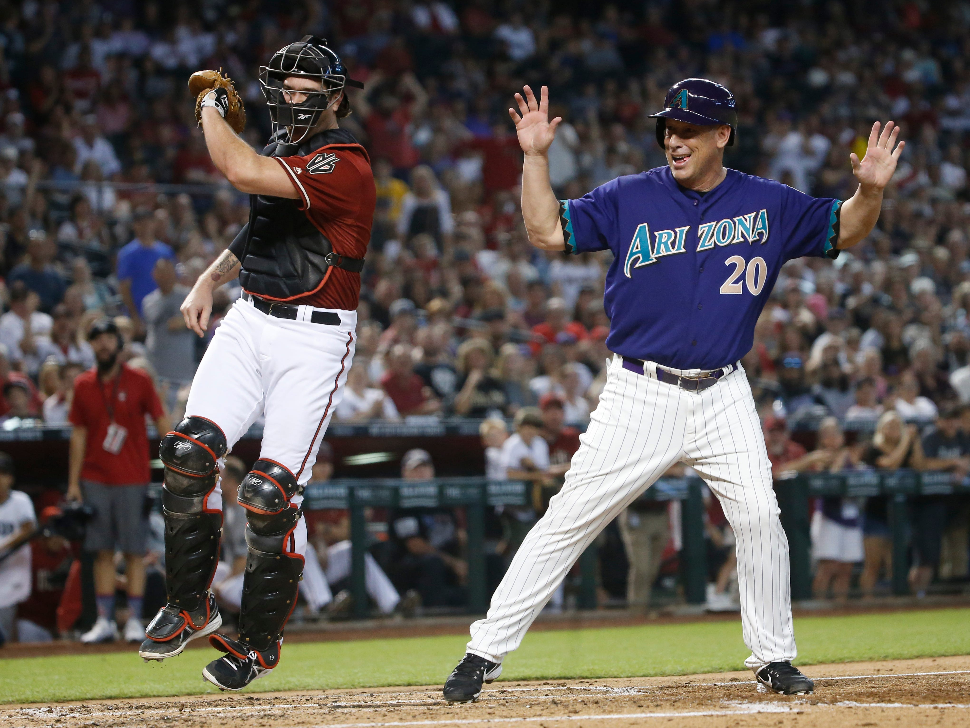 Diamondbacks Red team's Chris Snyder reacts after tagging out Purple team's Luis Gonzalez (20) during the Generations Diamondbacks Alumni game at Chase Field in Phoenix, Ariz. on Aug. 4, 2018.