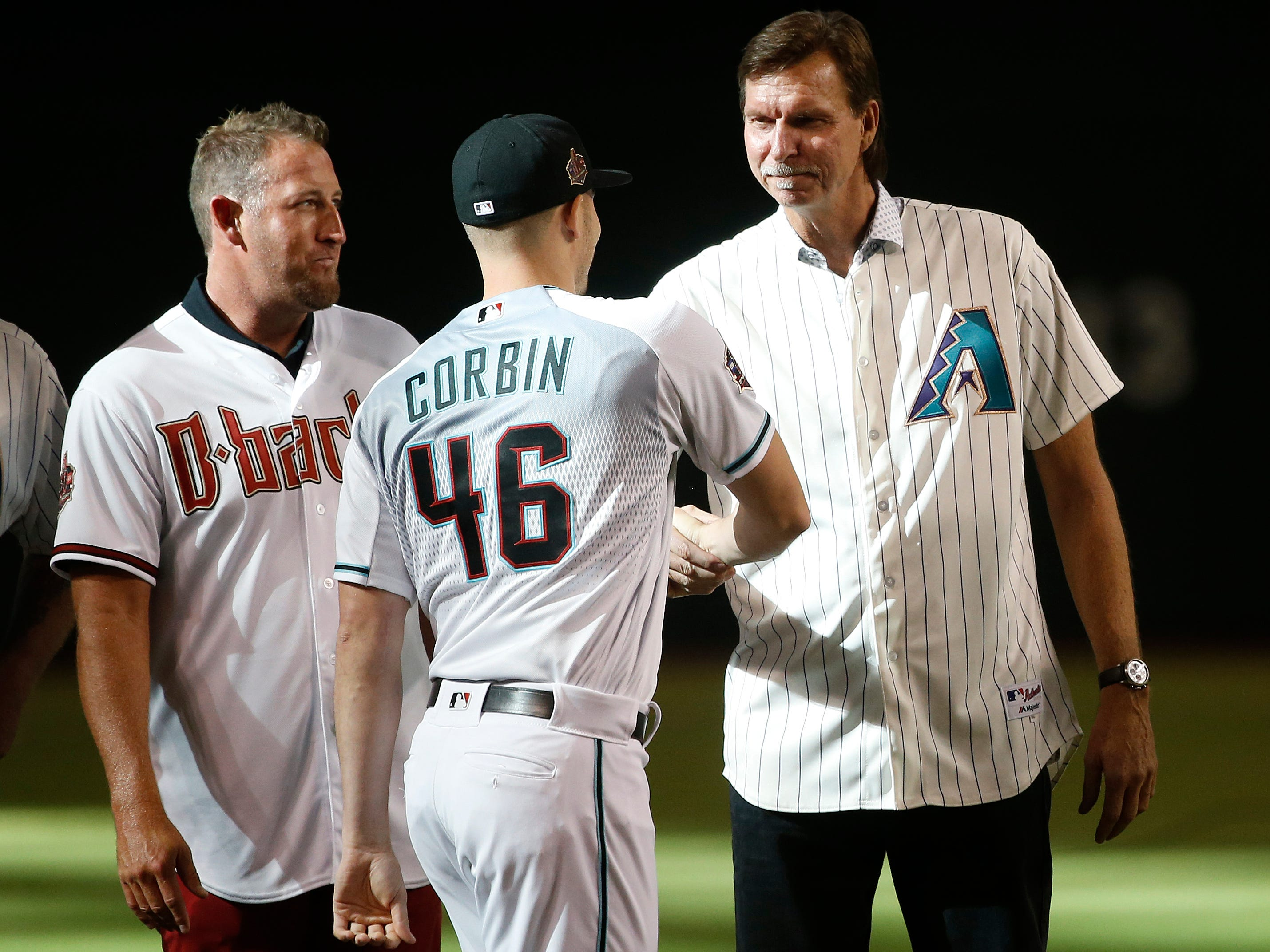 Diamondbacks legend Randy Johnson (R) greets current pitcher Patrick Corbin (46) at the mound as the players become members of the Diamondbacks 20th Anniversary team prior to a Diamondbacks game at Chase Field in Phoenix, Ariz. on Aug. 4, 2018.
