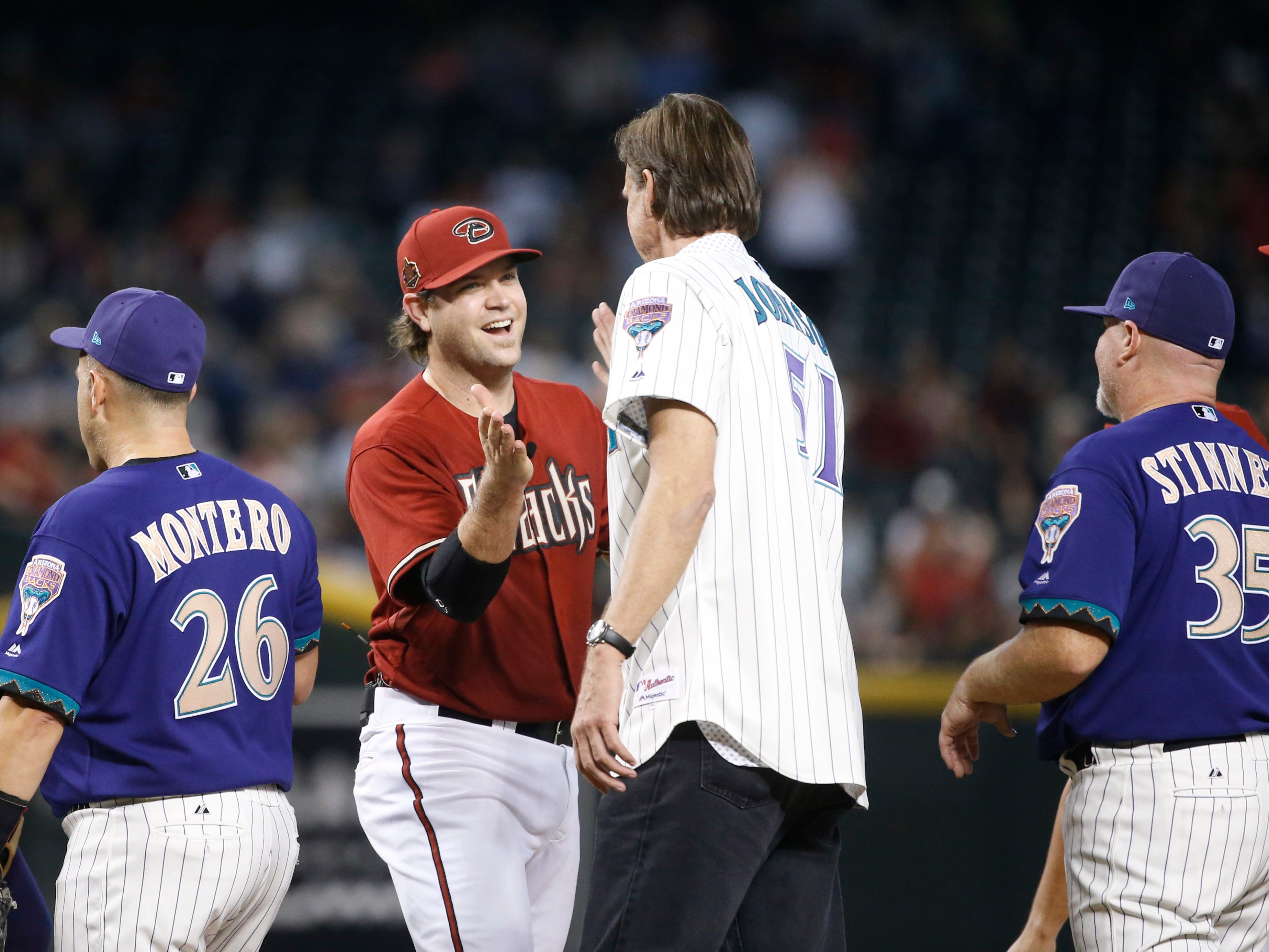 Diamondbacks Randy Johnson (51) high-fives Chris Snyder after the Generations Diamondbacks Alumni game at Chase Field in Phoenix, Ariz. on Aug. 4, 2018.