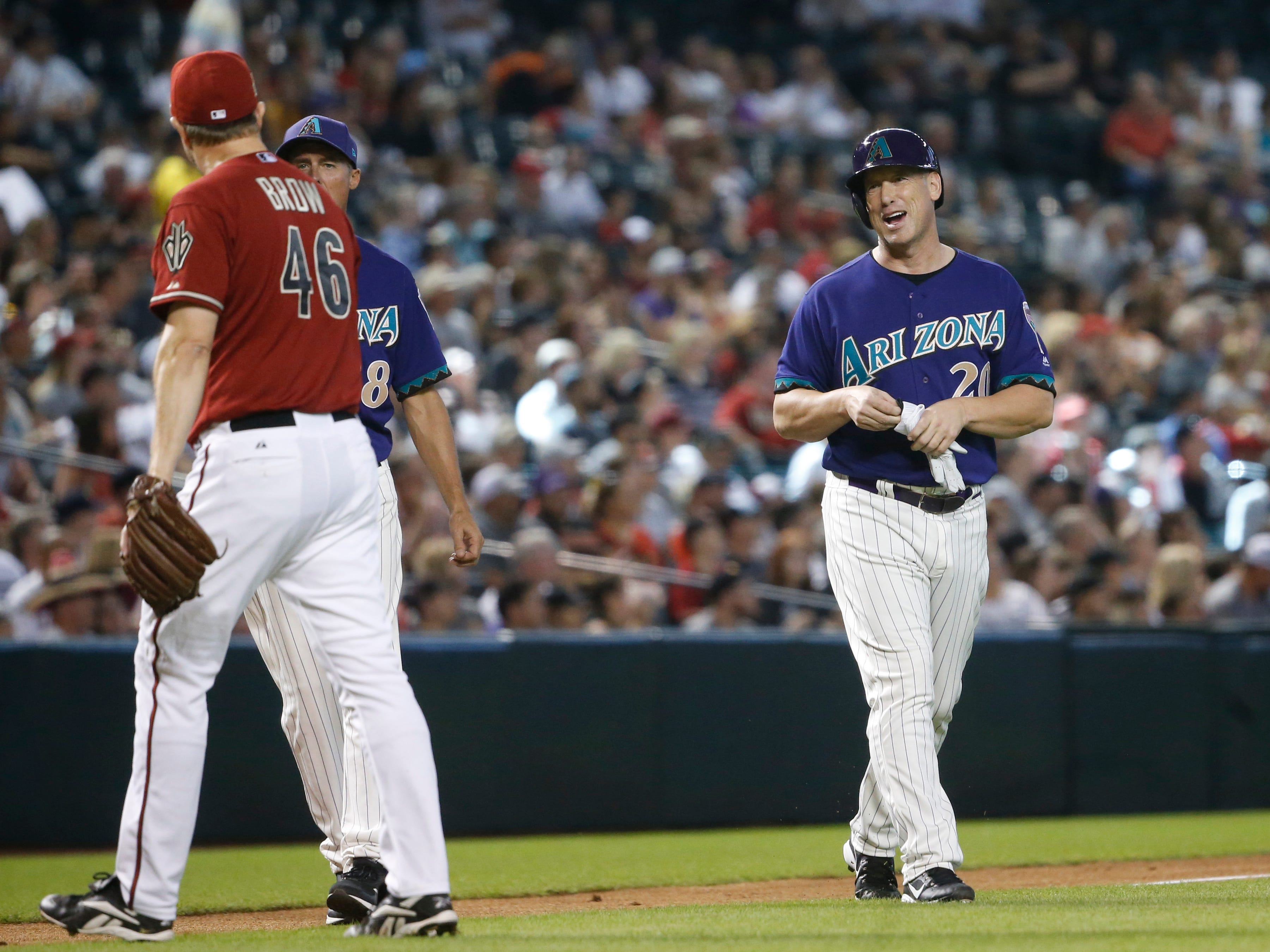 Diamondbacks Purple team's Luis Gonzalez (20) jokes with Red team's Scott Brow (46) during the Generations Diamondbacks Alumni game at Chase Field in Phoenix, Ariz. on Aug. 4, 2018.