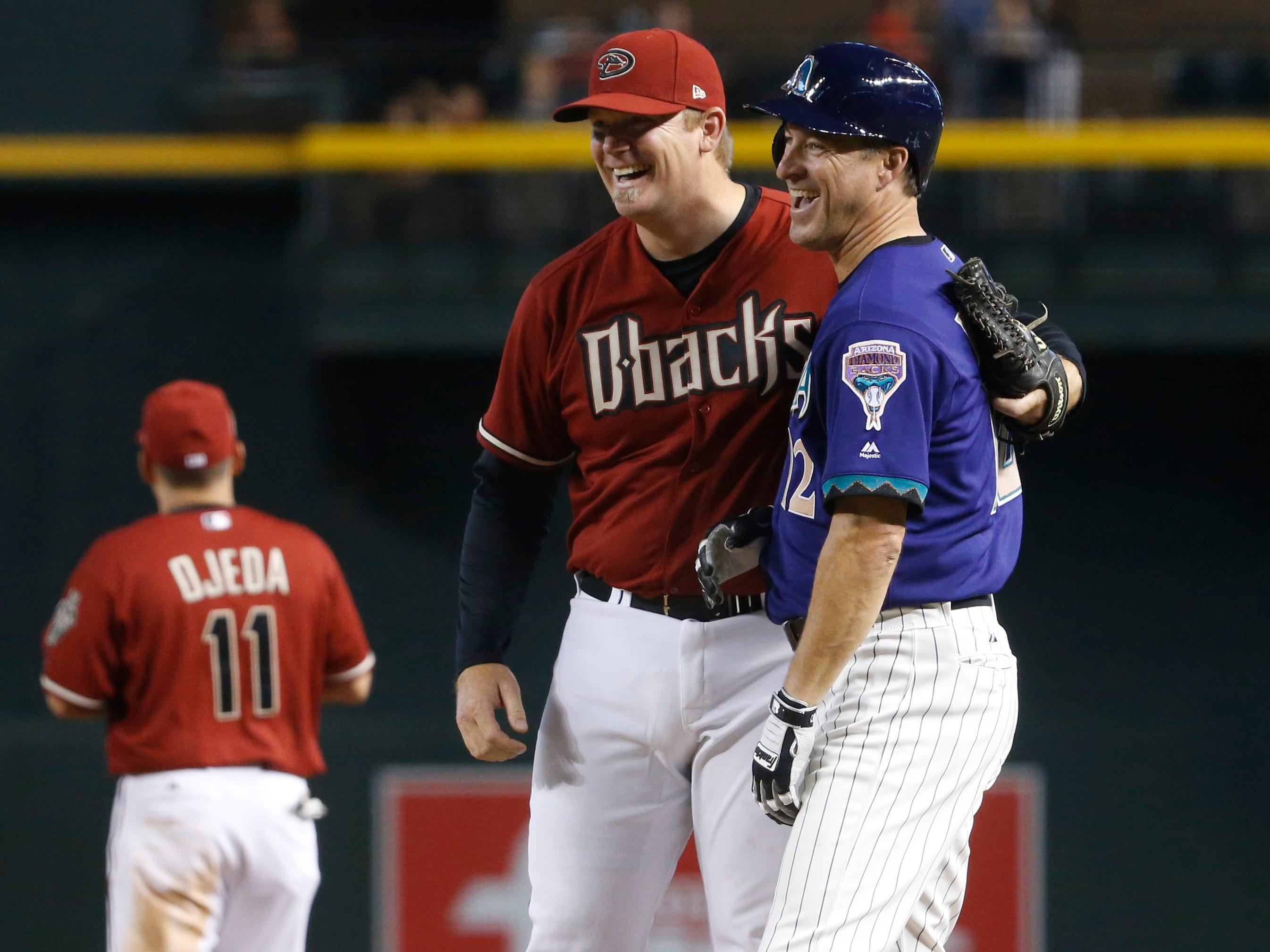Diamondbacks Red team's JJ Putz (L) hugs Purple team's Steve Finley (12) after Finley beat a throw of Putz's to first base during the Generations Diamondbacks Alumni game at Chase Field in Phoenix, Ariz. on Aug. 4, 2018.
