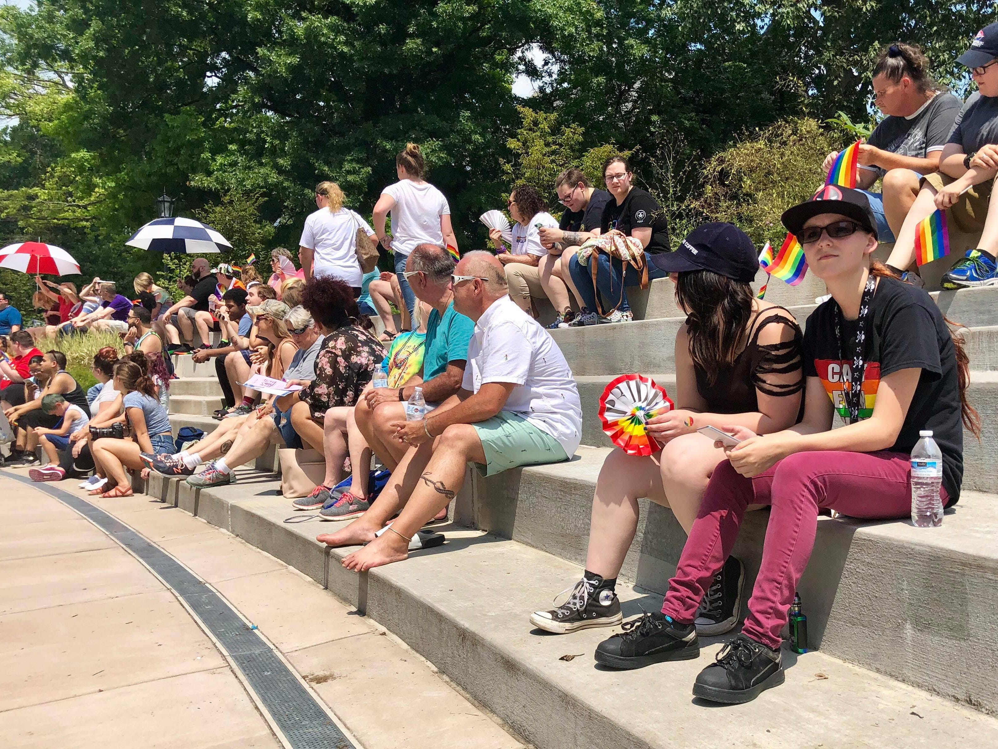 Attendees sit on the steps near the library at Wilson College in Chambersburg before the drag show starts during Franklin County's first Pride festival the afternoon of Sunday, Aug. 5, 2018.