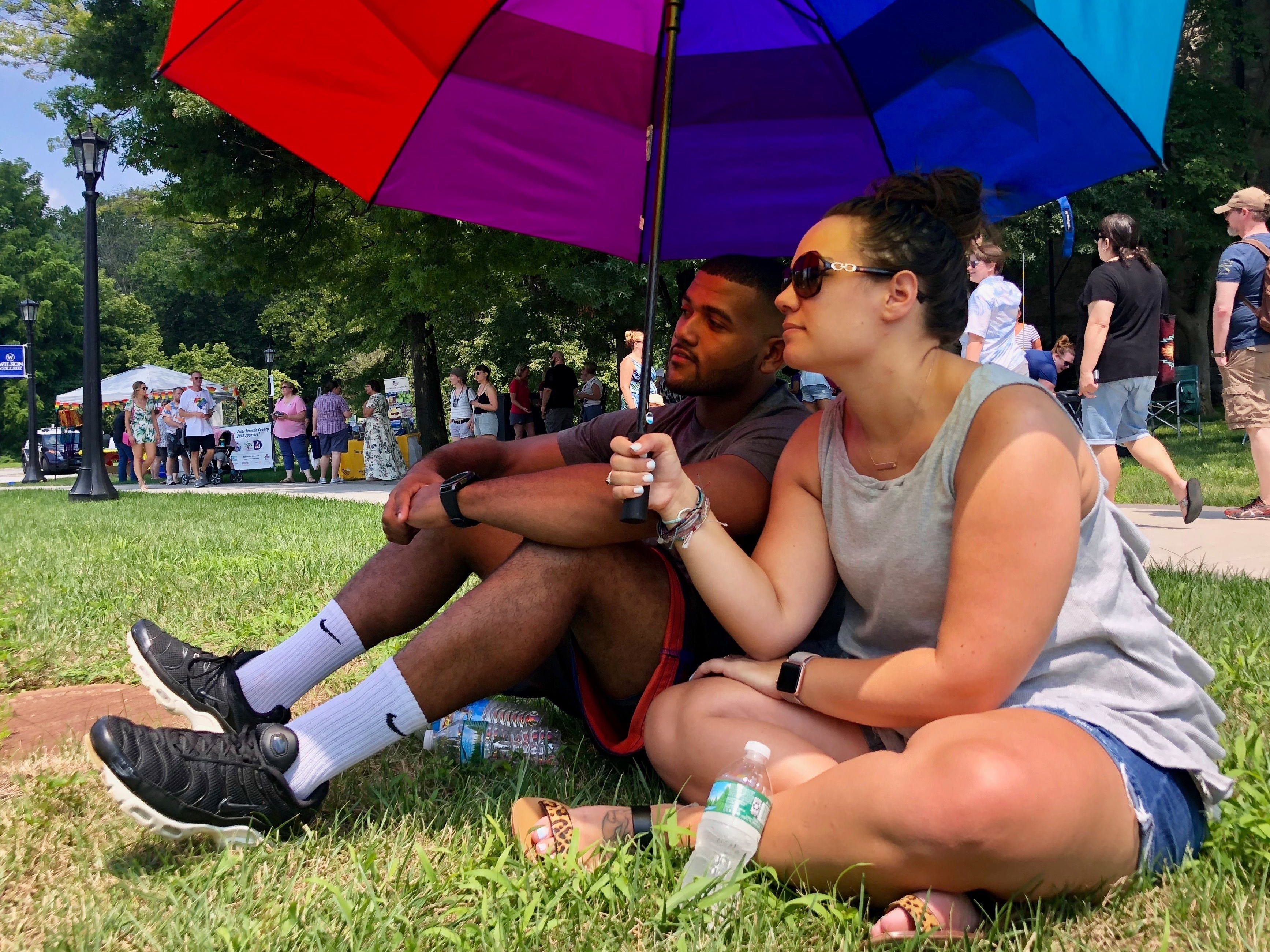 Two attendees sit under an umbrella and listen to a panel discussion during Franklin County's first Pride festival the afternoon of Sunday, Aug. 5, 2018 at Wilson College in Chambersburg.