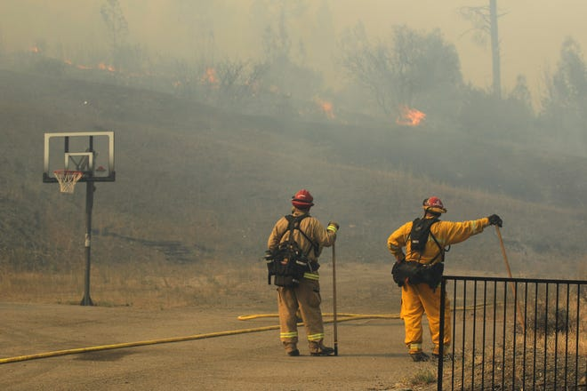 Fire Captains, Scott Long, left, and Jesse Carrales of Engine 8211 from the Monterey Fire Department keep their eyes on the Carr Fire burning in the back of the French Gulch Community Church on Saturday afternoon.  The fire flared up again on Saturday afternoon in the downtown section of French Gulch. The fire is burning in a portion of the west side of Main Street and the Clear Creek Mobile Estates and also behind the French Gulch Community Church property. (Special to the Record Searchlight photo by Hung T. Vu)
