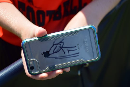 A student from Vinson Middle School in Huntington, W.Va., displays a cell-phone cover autographed by Houston Texans defensive end J.J. Watt during the team's preseason camp on Saturday, Aug. 5, 2018, at the Greenbrier in White Sulphur Springs, W.Va.