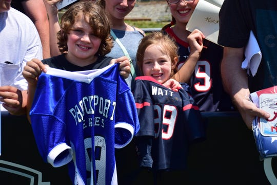 Fans display the memorabilia they got autographed by the Houston Texans during the team's preseason camp on Saturday, Aug. 5, 2018, at the Greenbrier in White Sulphur Springs, W.Va.