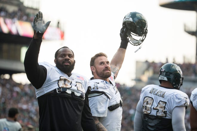 The Eagles' Fletcher Cox, left, and Chris Long wave to fans as they take the field for the first public practice of the season Sunday at Lincoln Financial Field.