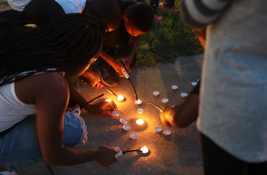 Candles are lit as mourners gather Saturday in a tribute to Ty'mire Selby, 12, who died in an accidental shooting at his home in the Riverside neighborhood of Wilmington on Friday.