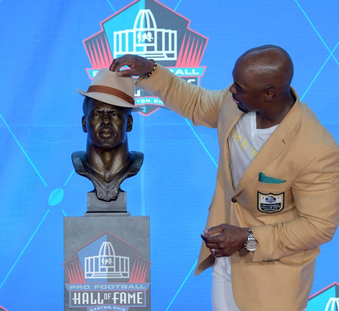 Former Philadelphia Eagles and Denver Broncos safety Brian Dawkins poses with his bust during the Pro Football Hall of Fame Enshrinement Ceremony at Tom Bensen Stadium.