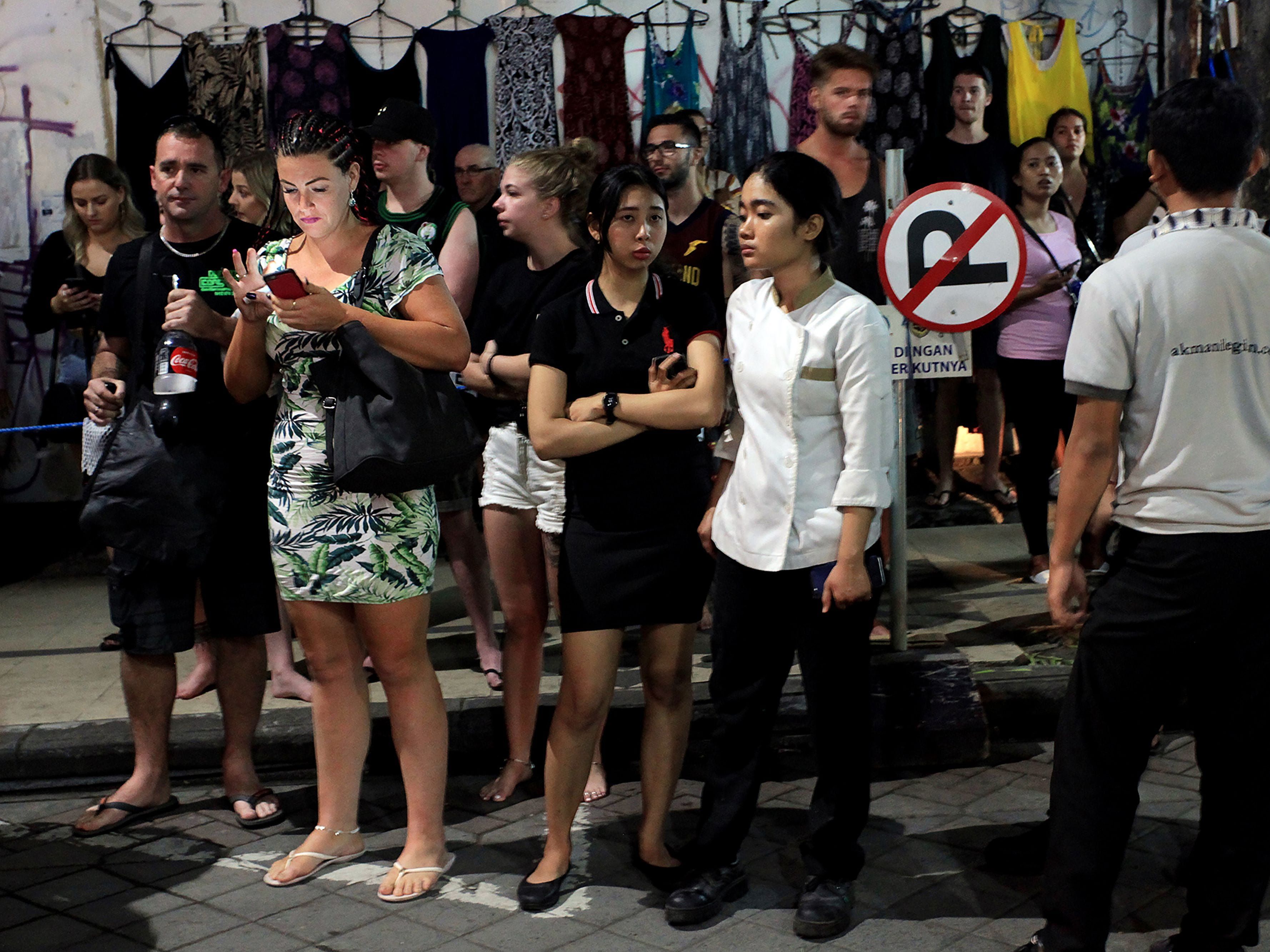 Foreign tourists and hotel staff stand on the street after being evacuated in Bali's capital Denpasar on Aug. 5, 2018, after a major earthquake rocked neighboring Lombok island.