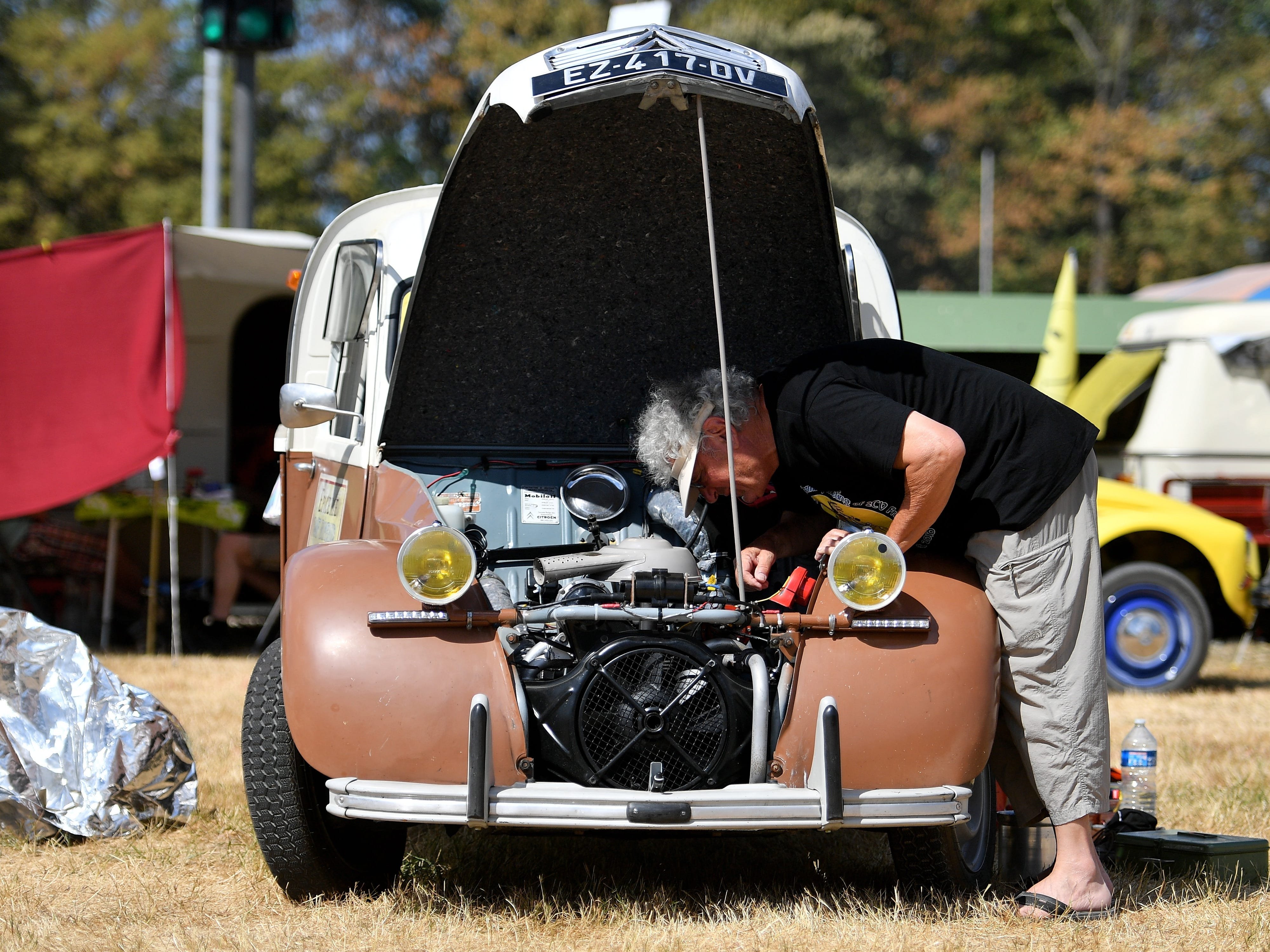 epa06928544 A man looks on the engine of a Citroen 2CV at the 8th International Germany Citroen 2CV meeting at the trotting track in Dinslaken, Germany, 05 August 2018. More than 1,000 fans of the French cult car from many countries, gazed numerous maintained examples of the cult 'duck' in all colours and versions.  EPA-EFE/SASCHA STEINBACH