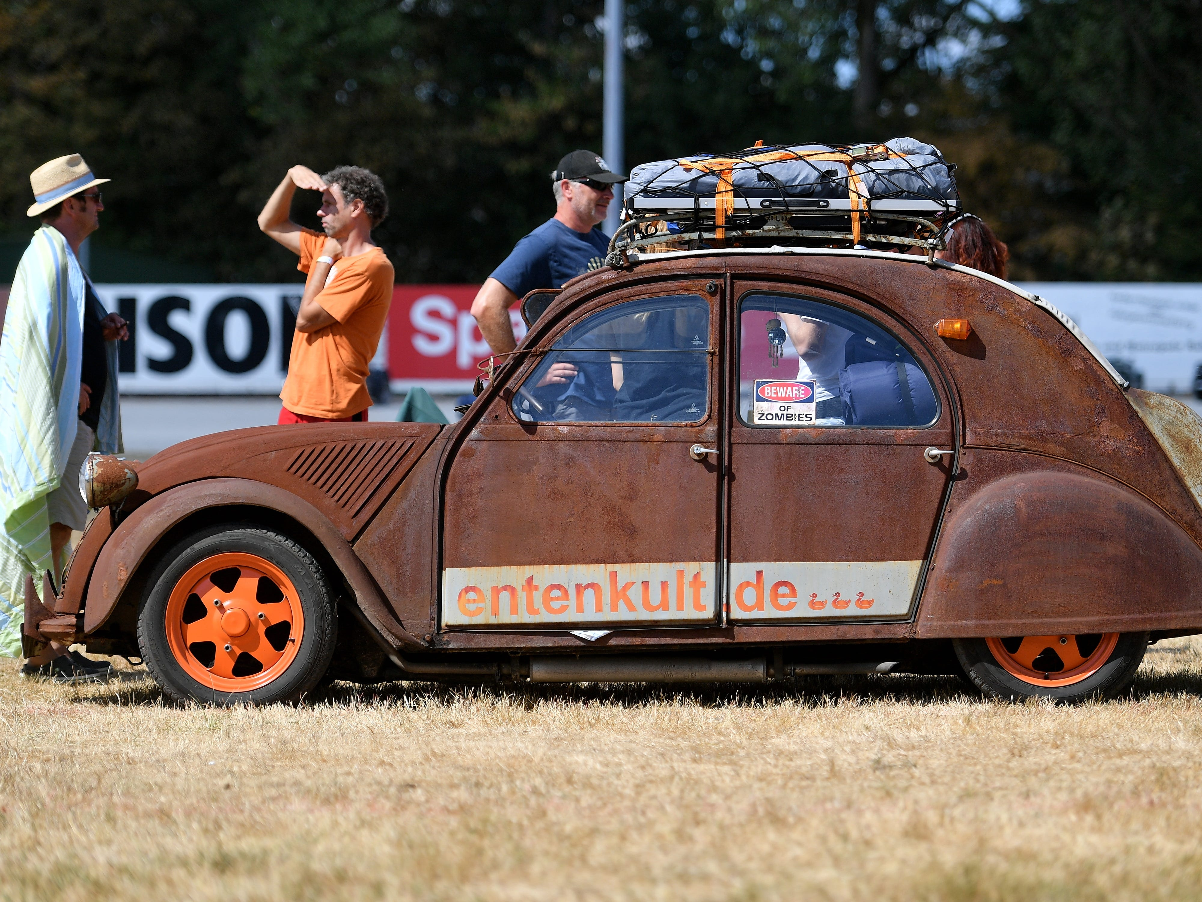 epa06928546 People stand next to Citroen 2CV at the 8th International Germany Citroen 2CV meeting at the trotting track in Dinslaken, Germany, 05 August 2018. More than 1,000 fans of the French cult car from many countries, gazed numerous maintained examples of the cult 'duck' in all colours and versions.  EPA-EFE/SASCHA STEINBACH