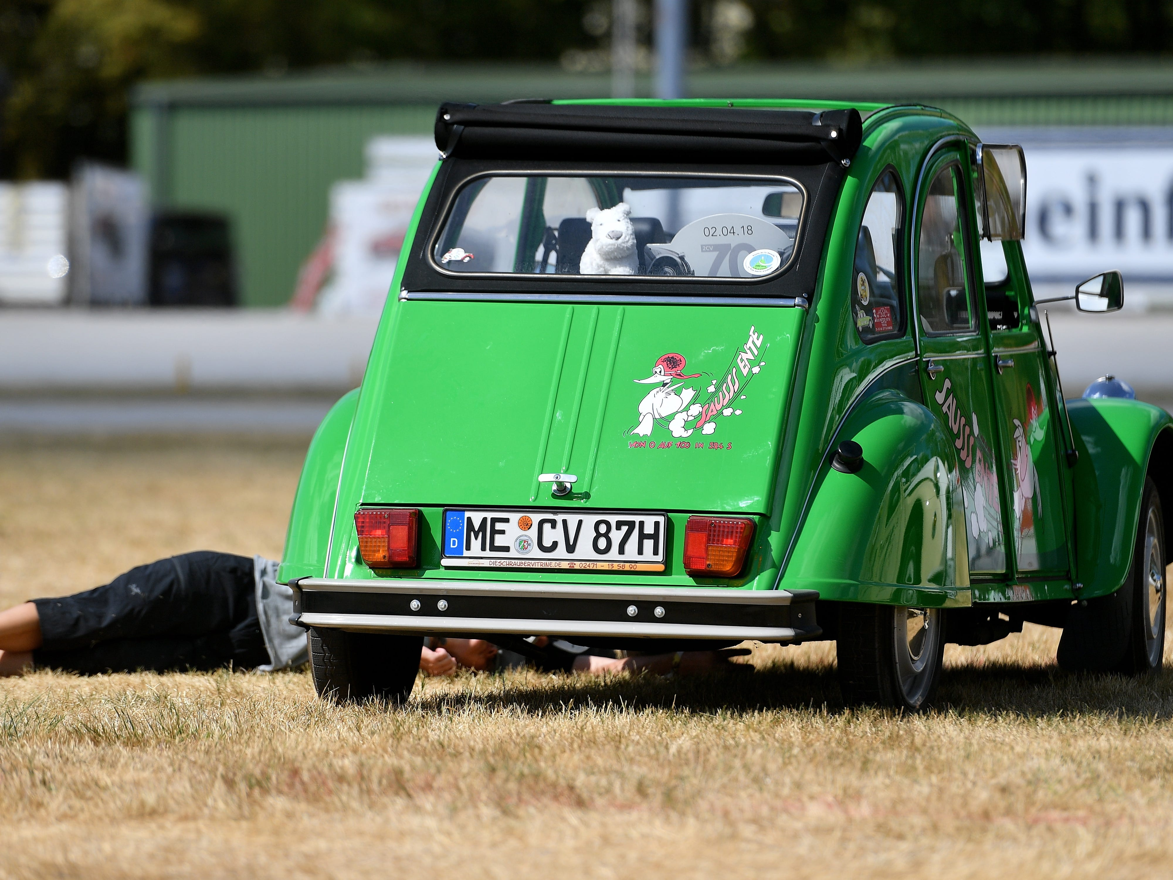 epa06928545 A man rests next to a Citroen 2CV at the 8th International Germany Citroen 2CV meeting at the trotting track in Dinslaken, Germany, 05 August 2018. More than 1,000 fans of the French cult car from many countries, gazed numerous maintained examples of the cult 'duck' in all colours and versions.  EPA-EFE/SASCHA STEINBACH