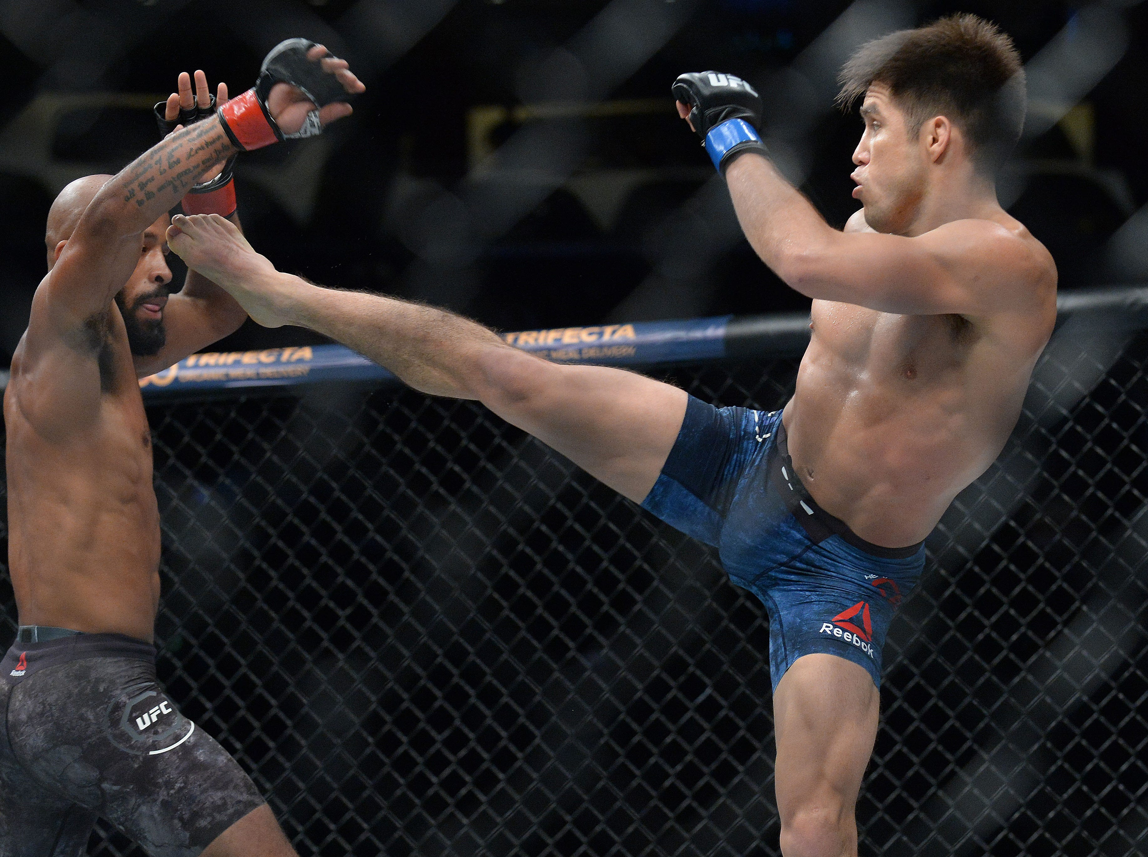 Henry Cejudo moves in with a kick against Demetrious Johnson during UFC 227 at Staples Center.