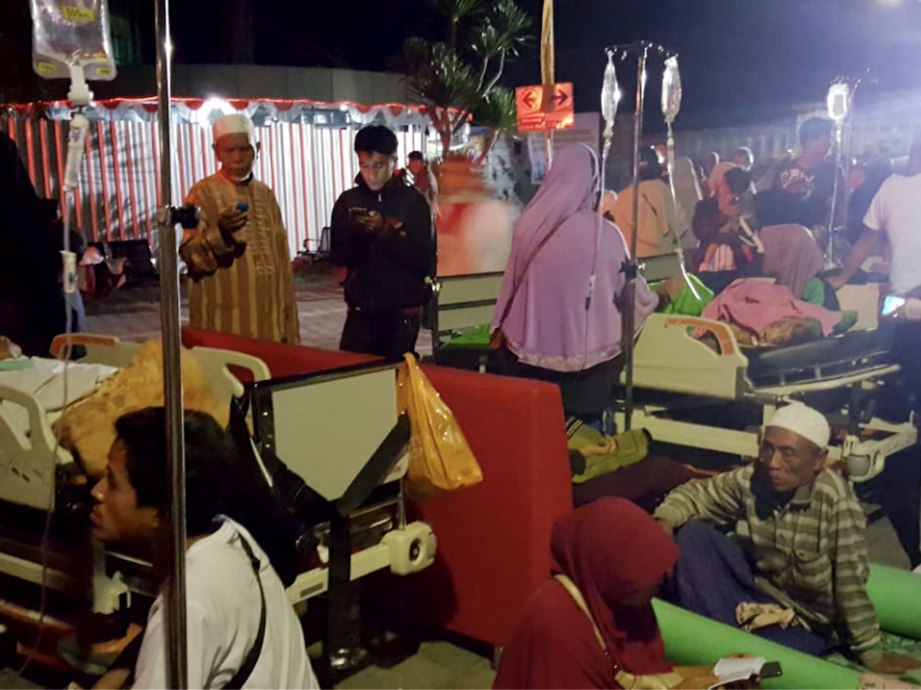 Hospital patients and relatives wait outside after being evacuated after an earthquake rocked Indonesia's Lombok island, in Mataram on Aug. 5, 2018.