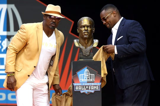 Pro Football Hall of Fame Class of 2018 enshrinee Brian Dawkins stands with Troy Vincent during the Pro Football Hall of Fame Enshrinement Ceremony at Tom Bensen Stadium.