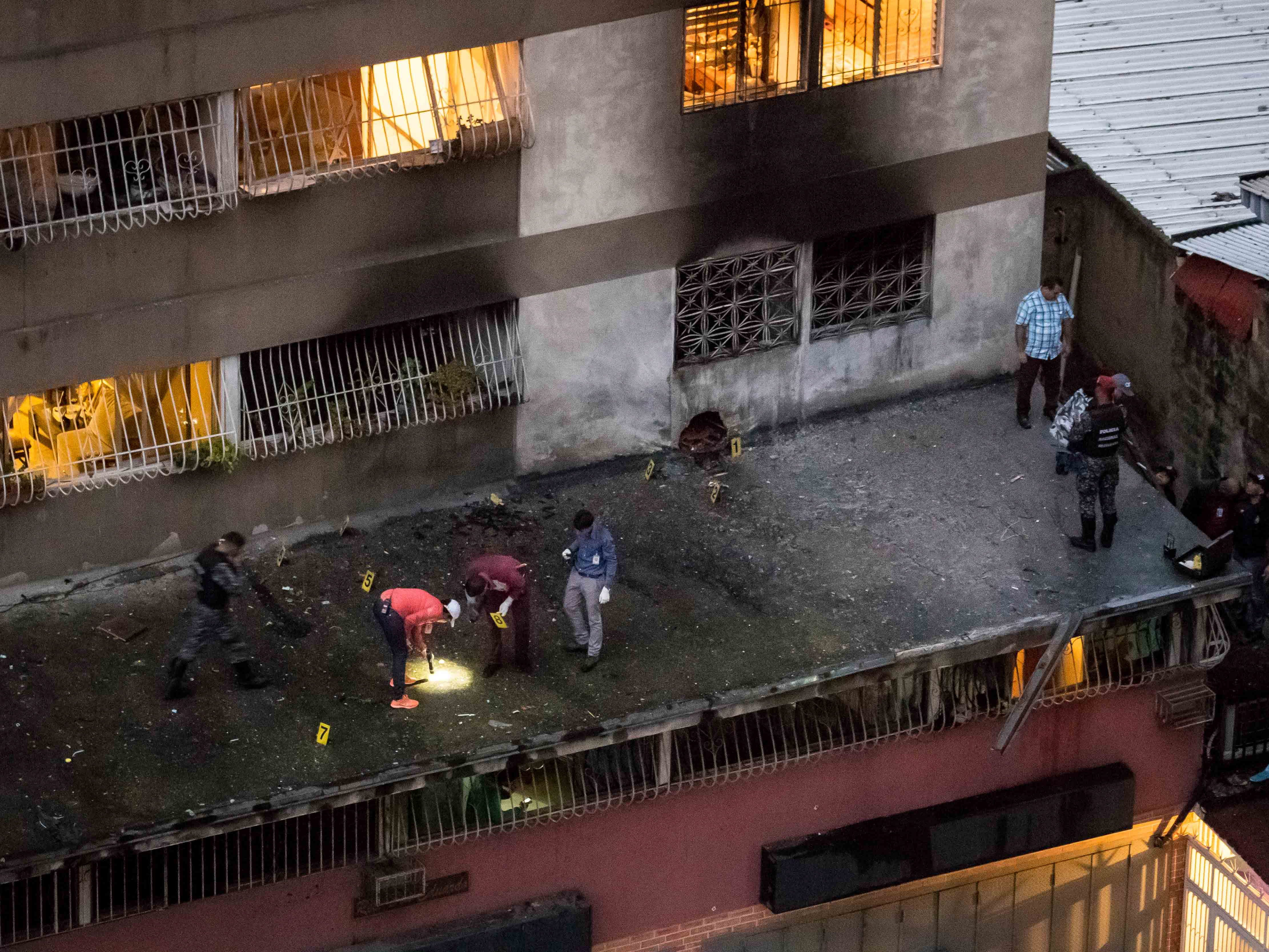 Members of different security forces stand guard and take evidence after an explosion targeted President Nicolas Maduro, in Caracas, Venezuela, 04 August 2018.