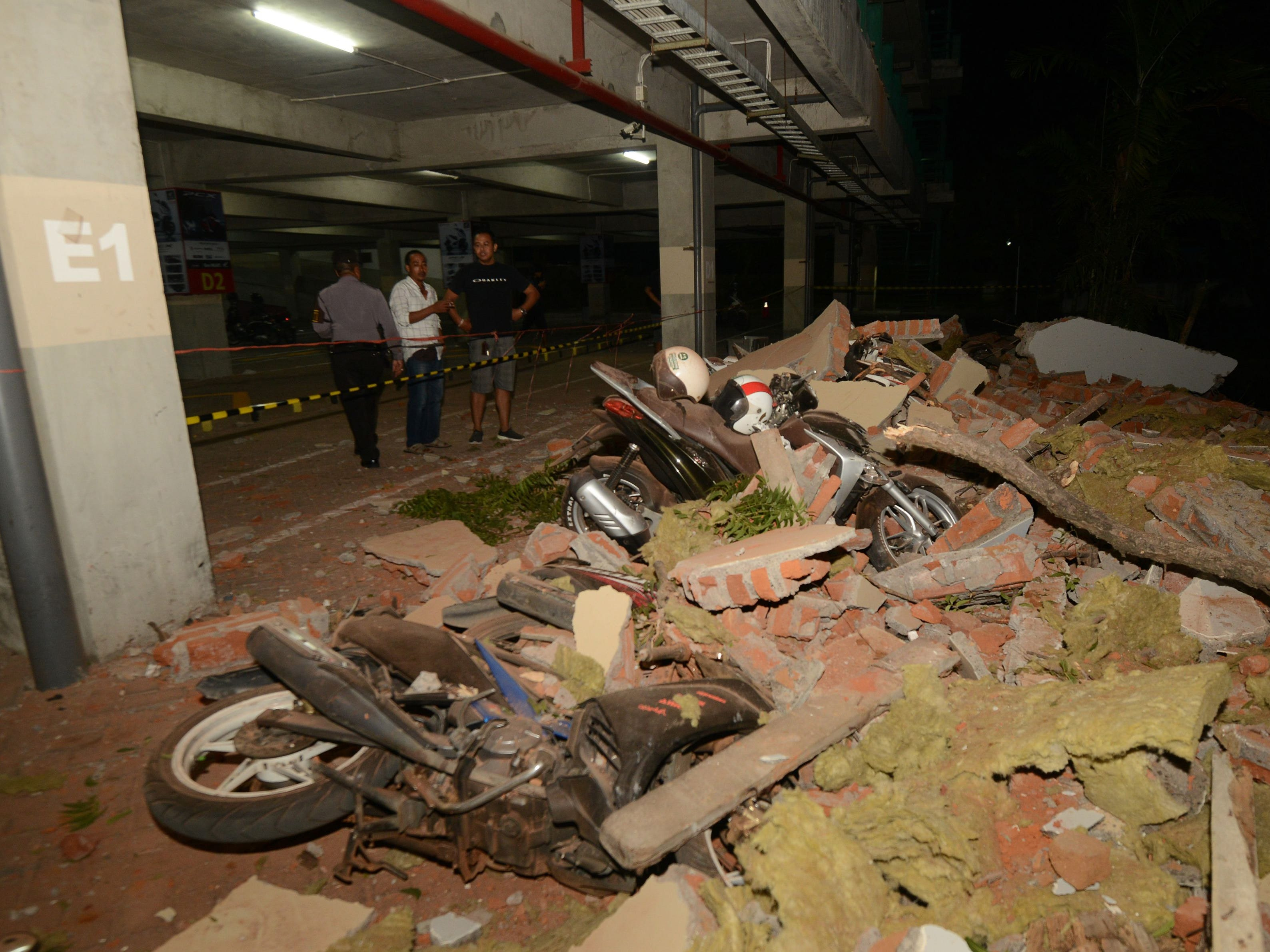 Residents look at bikes and debris at a mall in Bali's capital Denpasar on August 5, 2018 after a major earthquake rocked neighboring Lombok island.