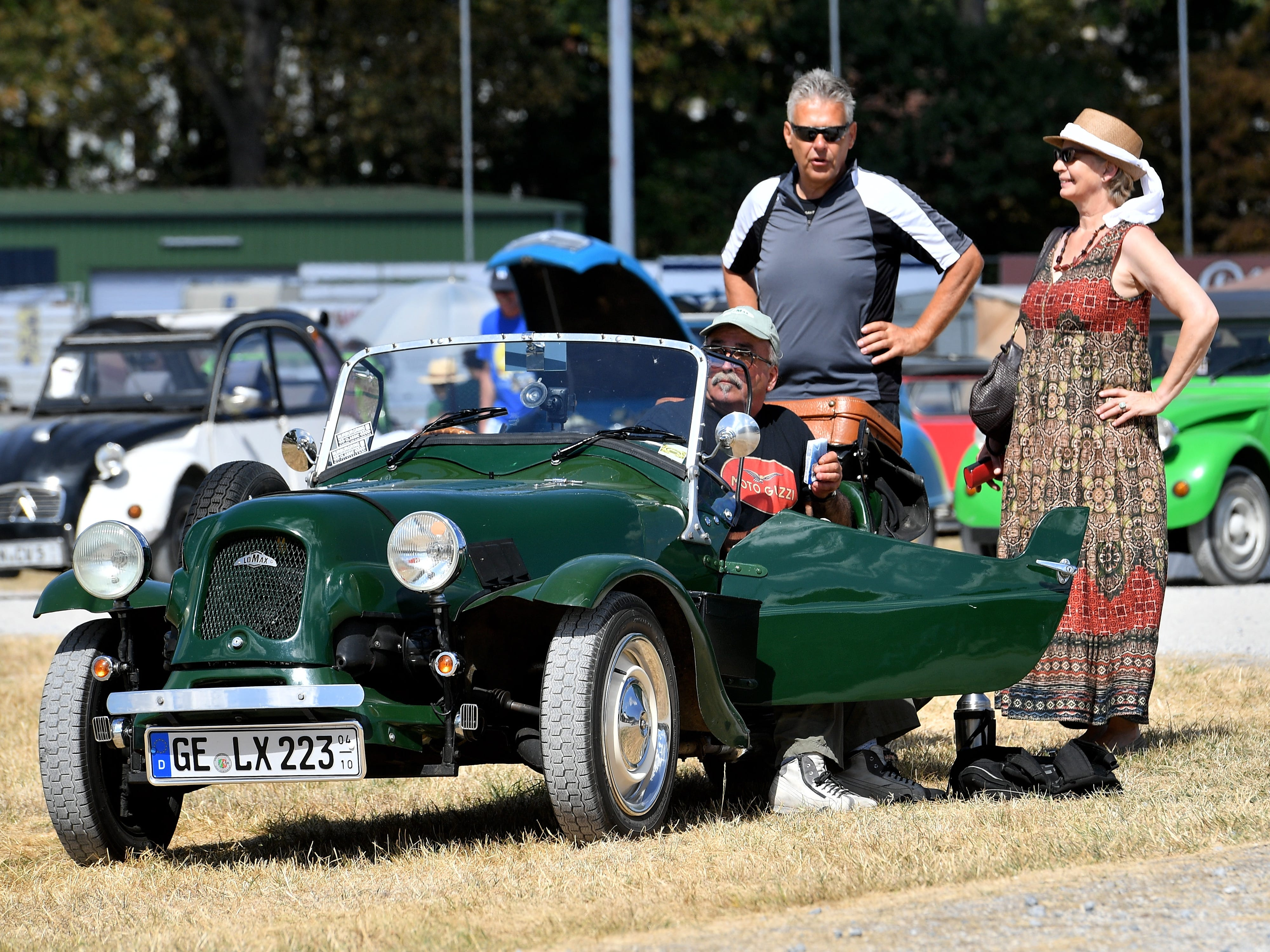 epa06928533 People look on a british Lomax car, based on a Citroen 2CV, at the 8th International Germany Citroen 2CV meeting at the trotting track in Dinslaken, Germany, 05 August 2018. More than 1,000 fans of the French cult car from many countries, gazed numerous maintained examples of the cult 'duck' in all colours and versions.  EPA-EFE/SASCHA STEINBACH