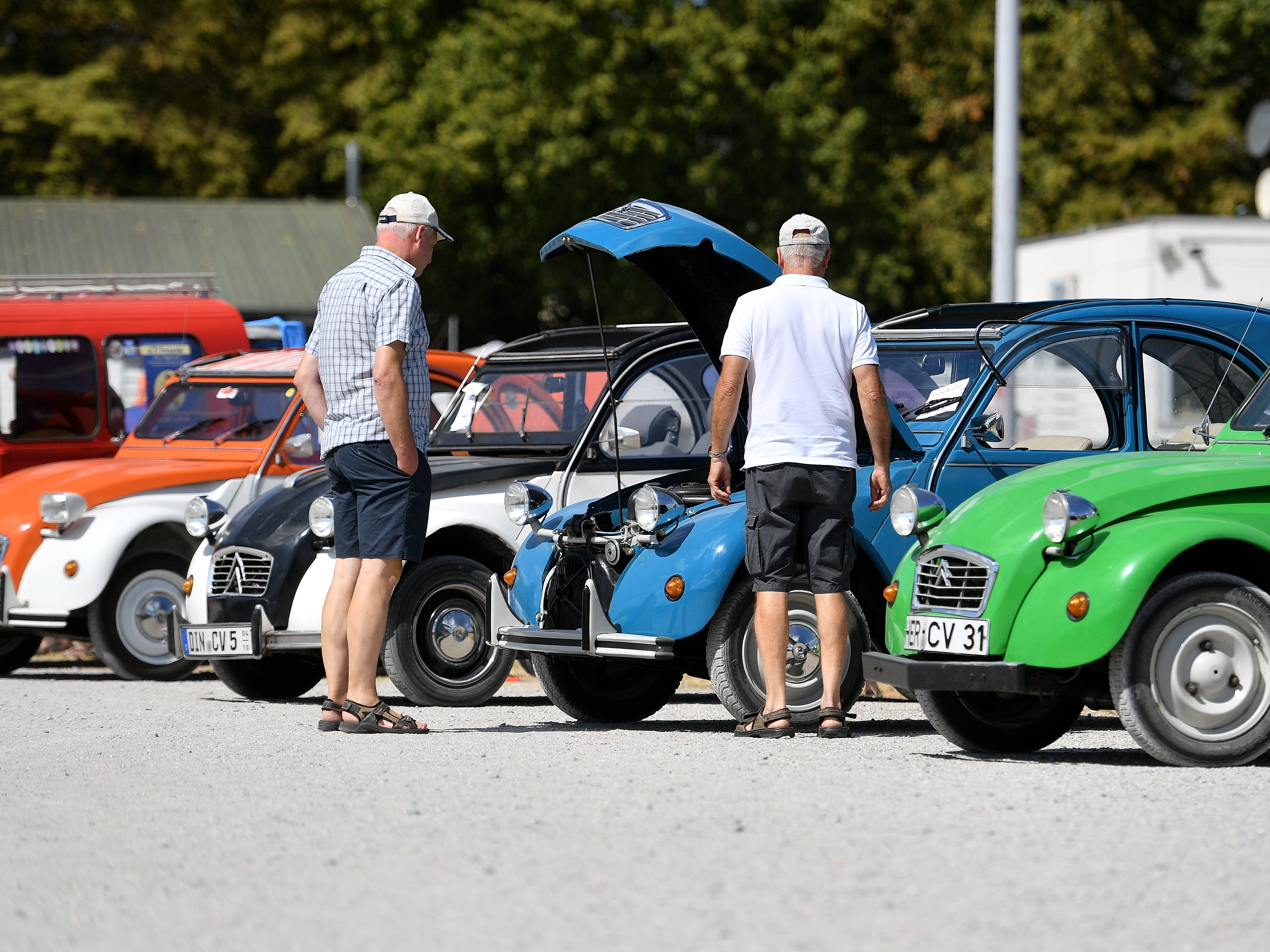 epa06928543 People stand next to Citroen 2CV cars at the 8th International Germany Citroen 2CV meeting at the trotting track in Dinslaken, Germany, 05 August 2018. More than 1,000 fans of the French cult car from many countries, gazed numerous maintained examples of the cult 'duck' in all colours and versions.  EPA-EFE/SASCHA STEINBACH