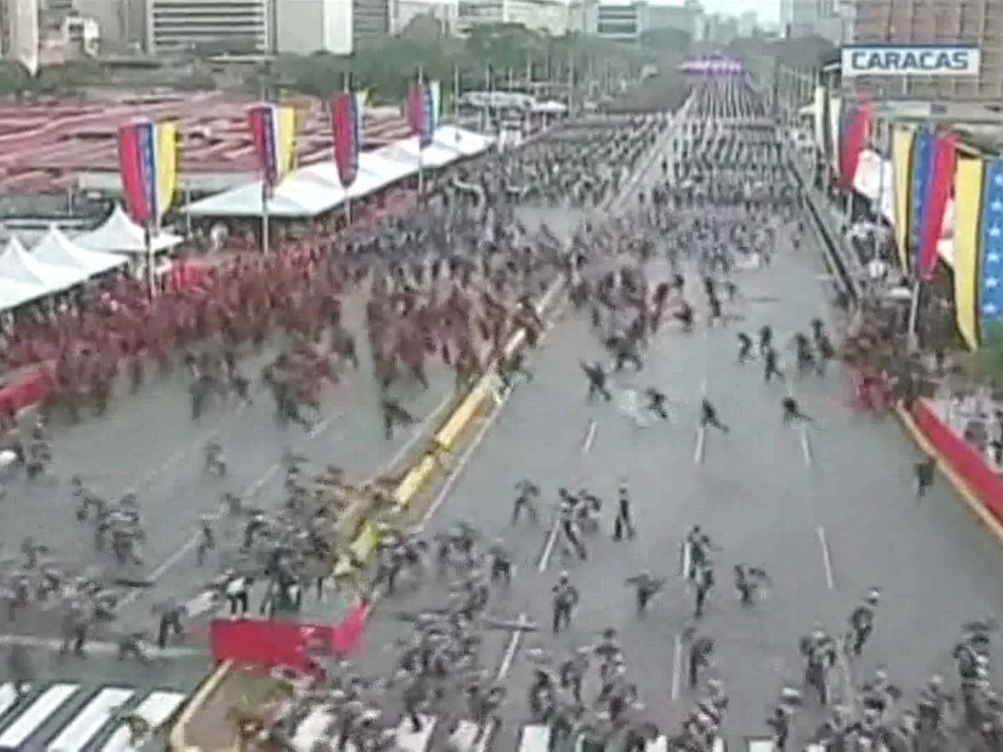 A handout screengrab taken from a video provided by Venezolana de Television (VTV), shows the moment in which a tv broadcast shows the military breaking ranks during the commemoration of the 81th anniversary of the creation of the Bolivarian National Guard (GNB), in Caracas, Venezuela on August 4, 2018. The hundreds of soldiers participating in the event ran after an evacuation warning after the detonation of 'drone-type flying devices that contained an explosive charge'. The Venezuelan President Nicolas Maduro was allegedly the intended target of the attack. During a speech after the attack, Maduro claimed that the Colombian President Juan Manuel Santos, and far-right elements in Venezuela had attempted to assassinate him using a pair of drones flying over the military ceremony. The resulting explosion injured seven people.