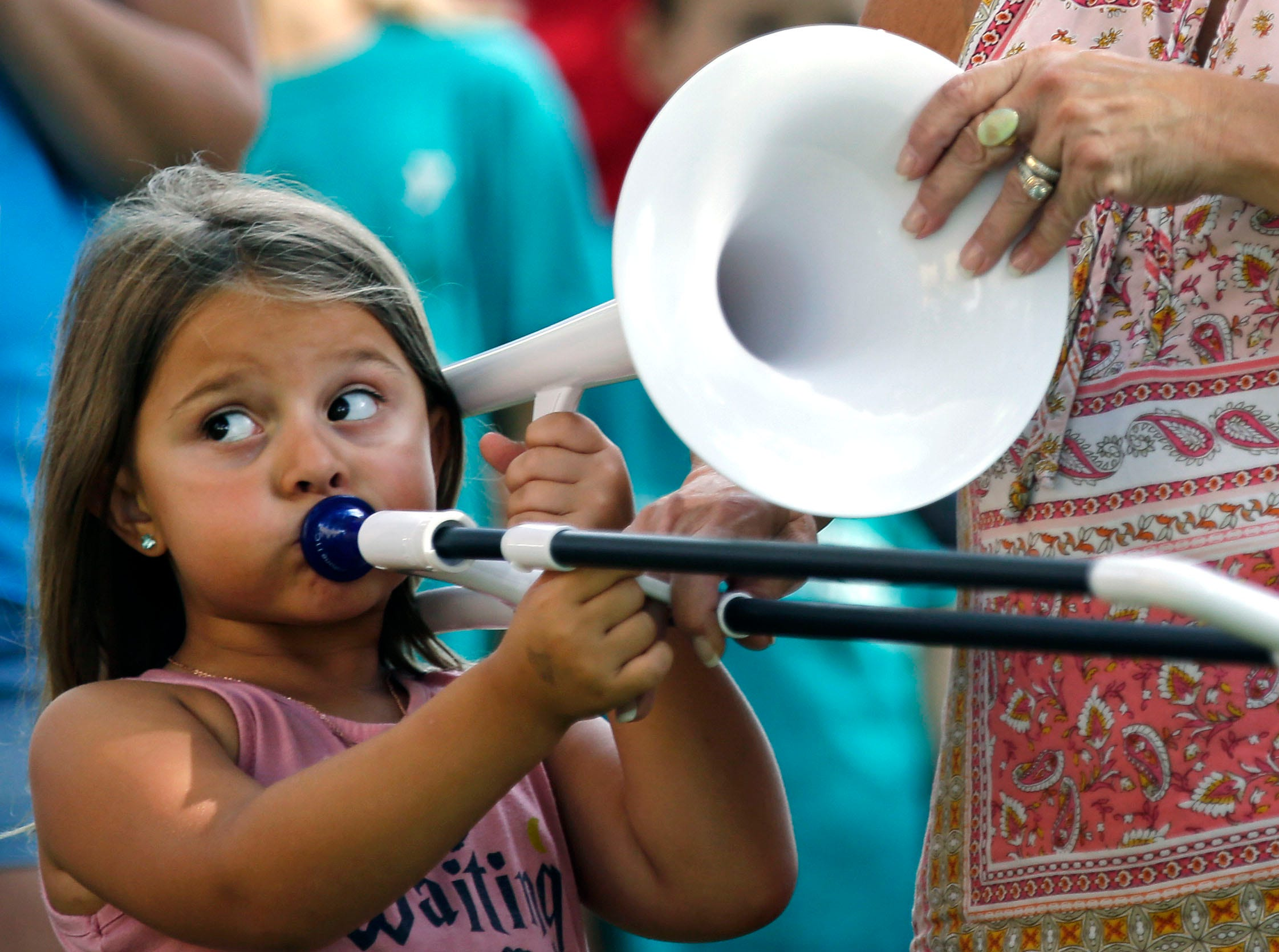 Elena Fiebelkorn gets helps holding the trombone from her grandmother, Suzi Perlewitz as Mile 6, the Mile of Music festival takes place Saturday, August 4, 2018, in Appleton, Wis.