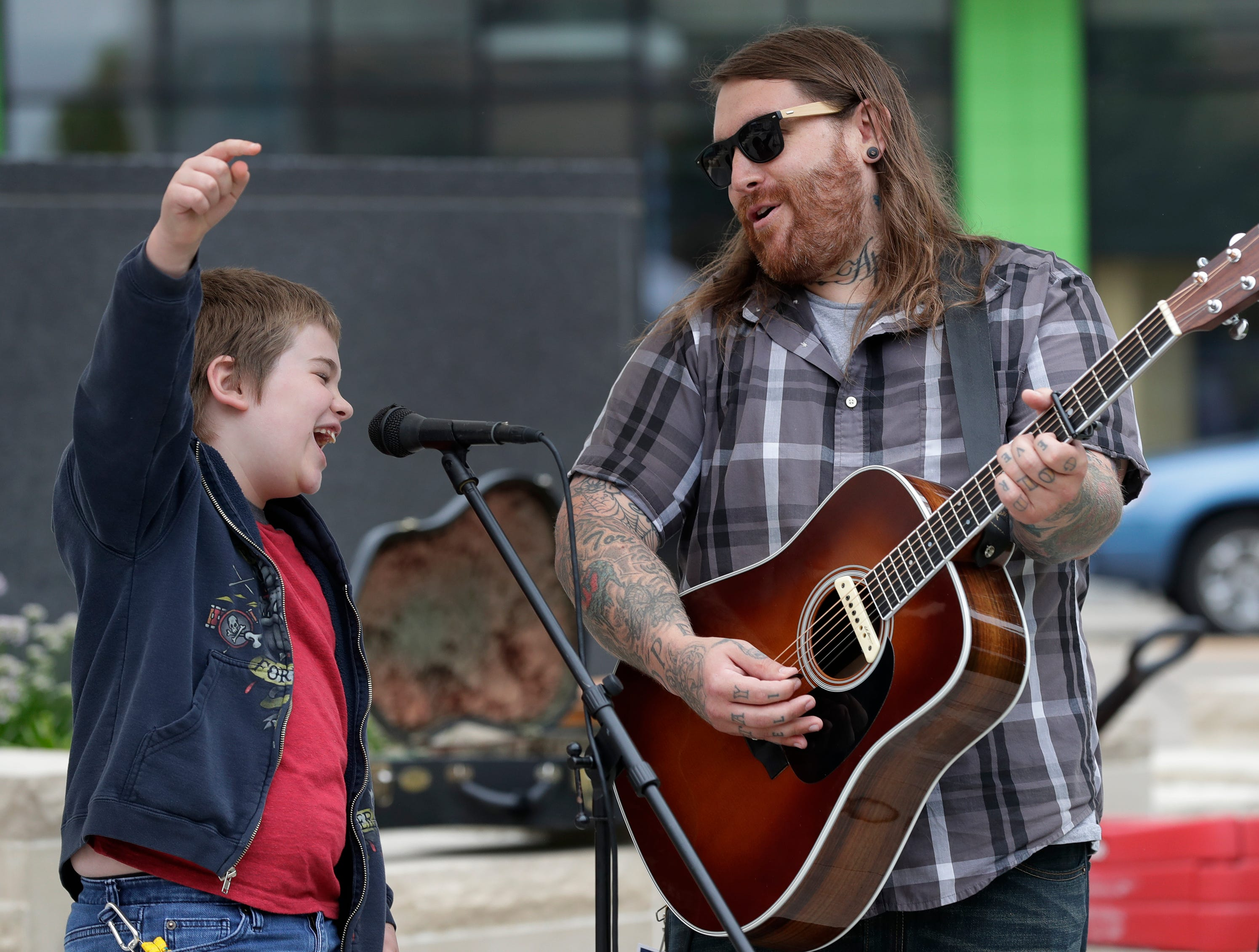 Oliver Gold, 9, left, performs a duet with his father Christopher Gold at Houdini Plaza during the Mile of Music Thursday, August 2, 2018, in Appleton, Wis.  