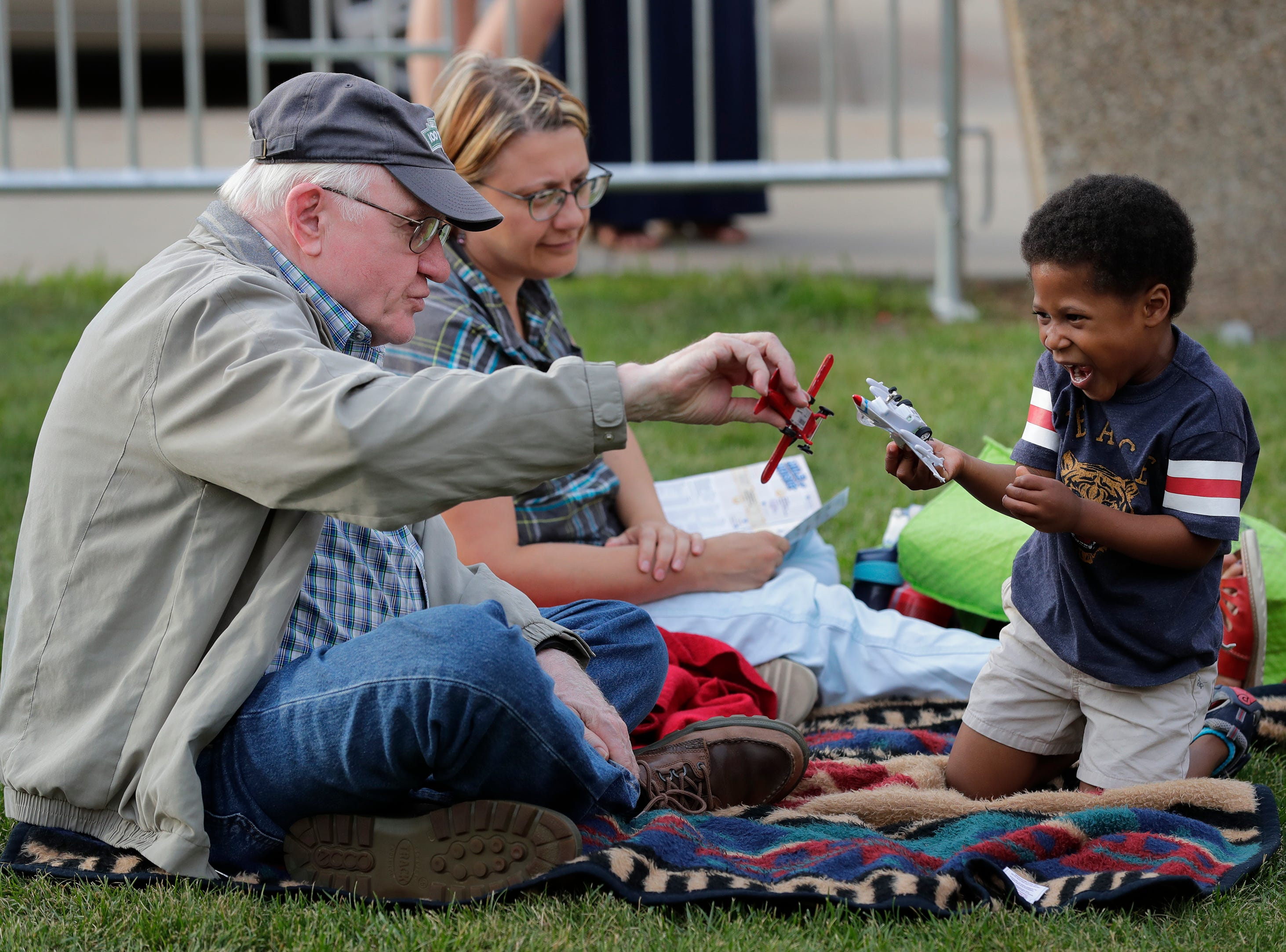 Don Feldkamp, left, of Appleton plays with his grandson Aiden Feldkamp, 4, while waiting for the start of a concert at Washington Square during the Mile of Music Friday, August 3, 2018, in Appleton, Wis.  In back is Aiden's mother Diane Feldkamp.