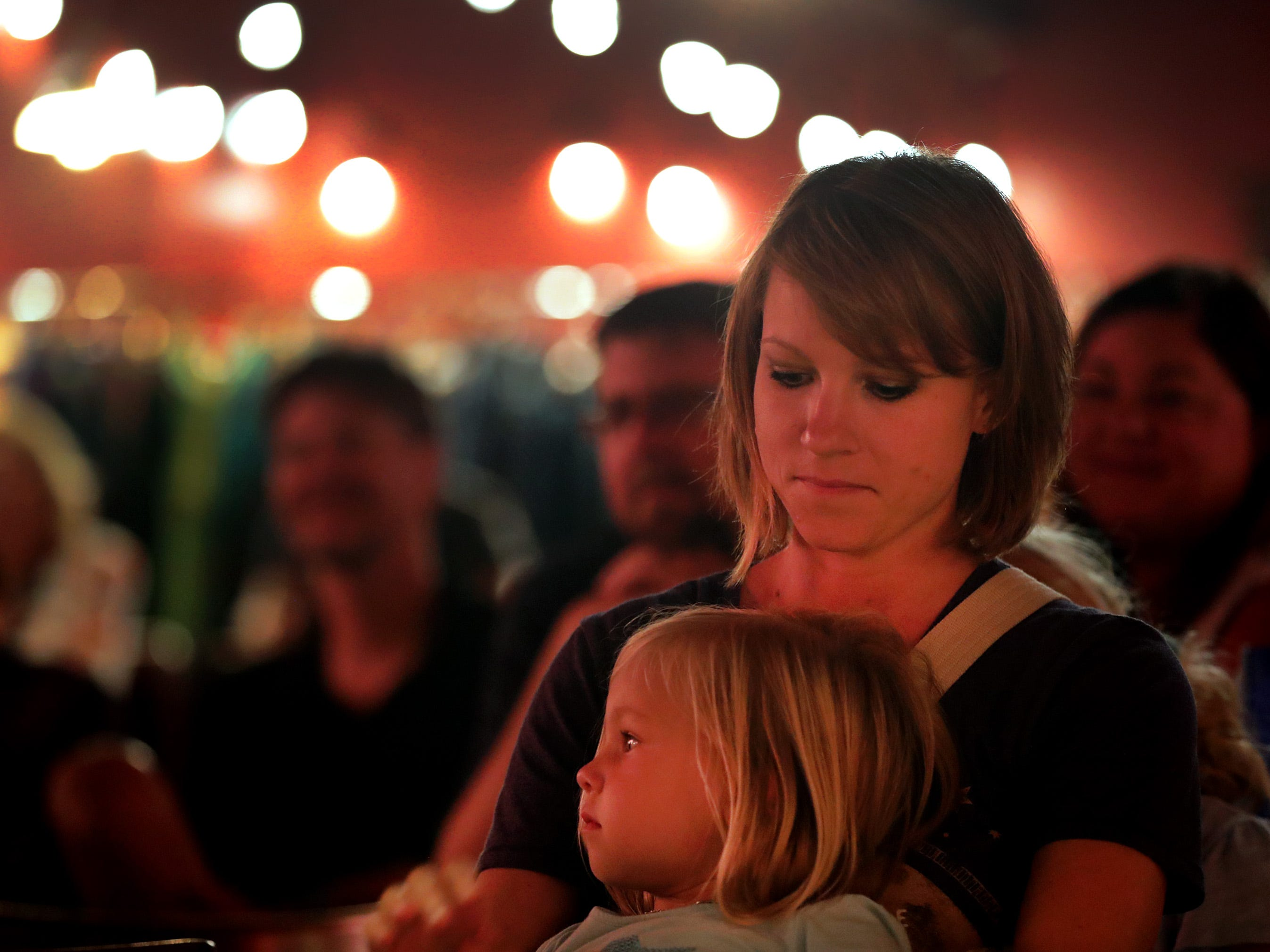 Rae and Ani Ammerman listen to The Suitcase Junket perform a pop-up show at the shared space of Forty Thee Skulls and Dave Jackson, the former Kat Su Ya building, during the Mile of Music festival Friday, August 3, 2018, in Appleton, Wis. 