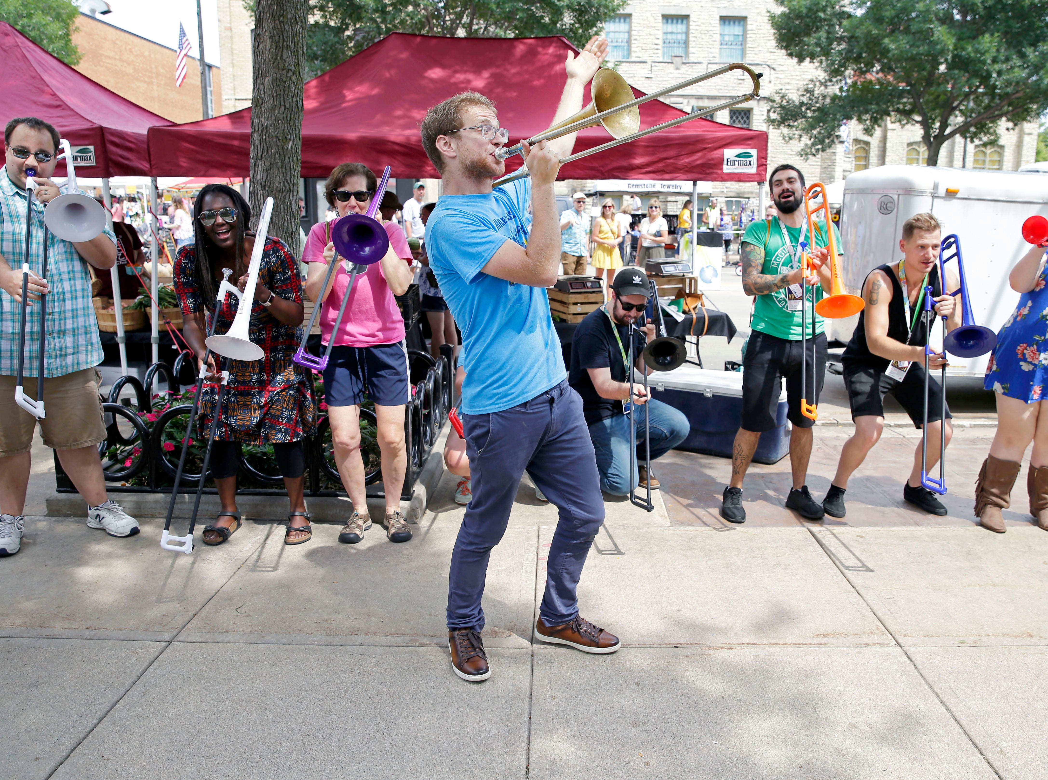 Ilan Blanck of Porky's Groove Machine directs a horn section of trainees during the Funk Band Jam as Mile 6, the Mile of Music festival takes place Saturday, August 4, 2018, in Appleton, Wis.