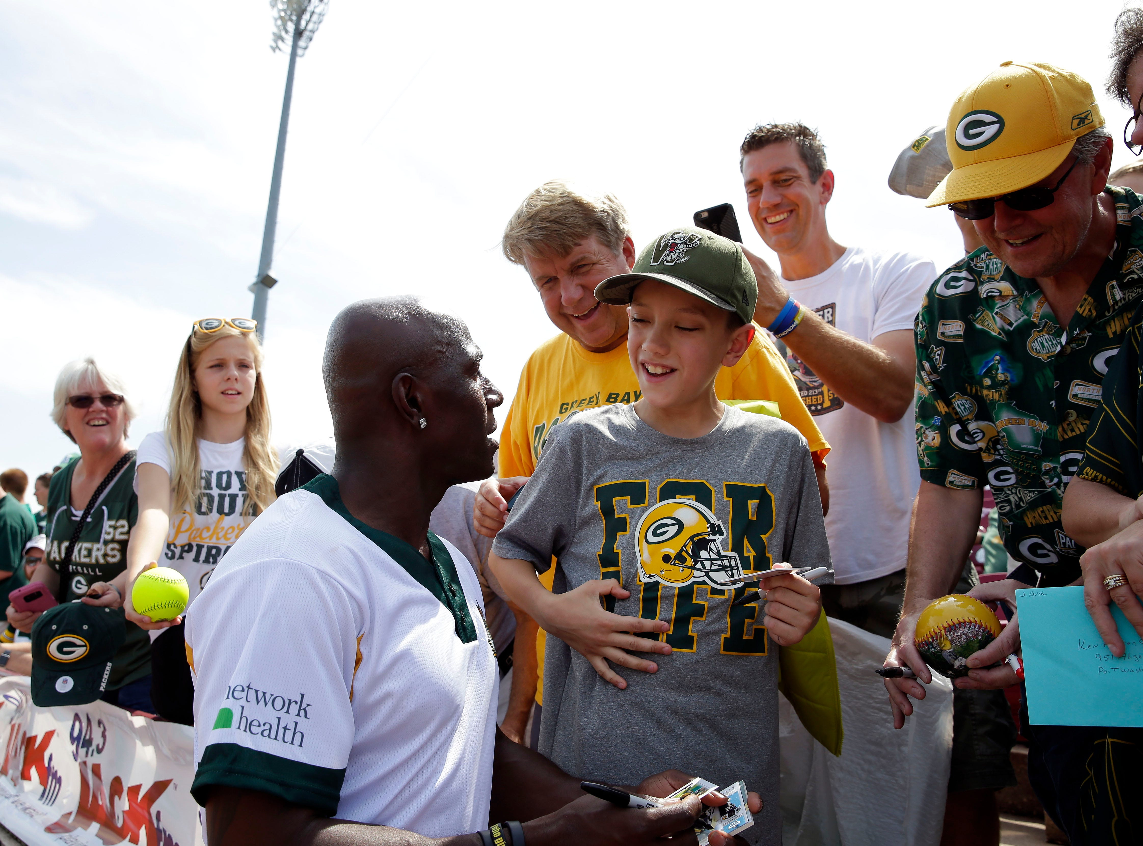 Lincoln Derks of Neenah talks with Donald Driver before the charity softball game Sunday, August 5, 2018, at Neuroscience Group Field at Fox Cities Stadium in Grand Chute, Wis.