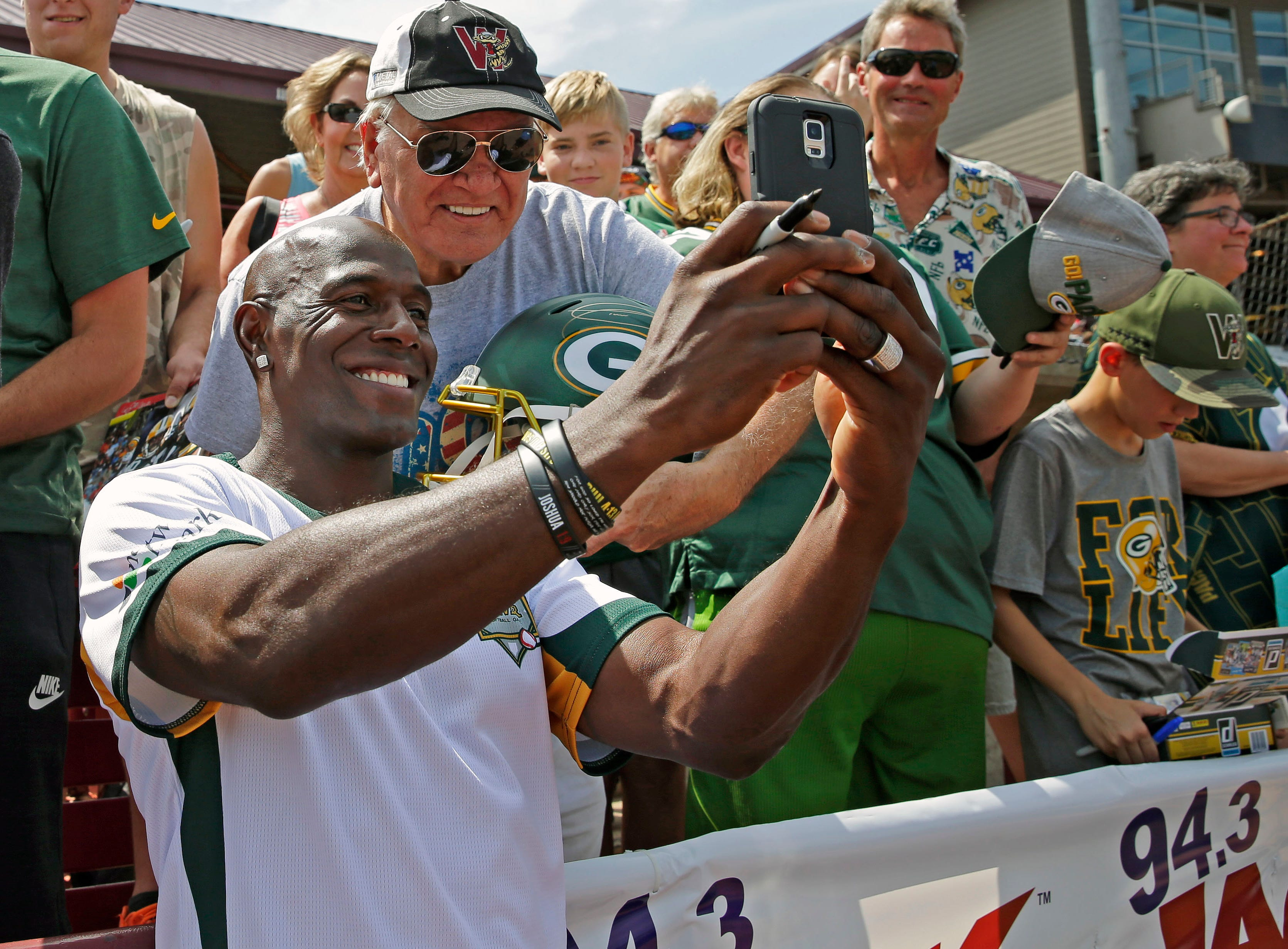 Ollie Brien gets a photo with Donald Driver before the charity softball game Sunday, August 5, 2018, at Neuroscience Group Field at Fox Cities Stadium in Grand Chute, Wis.