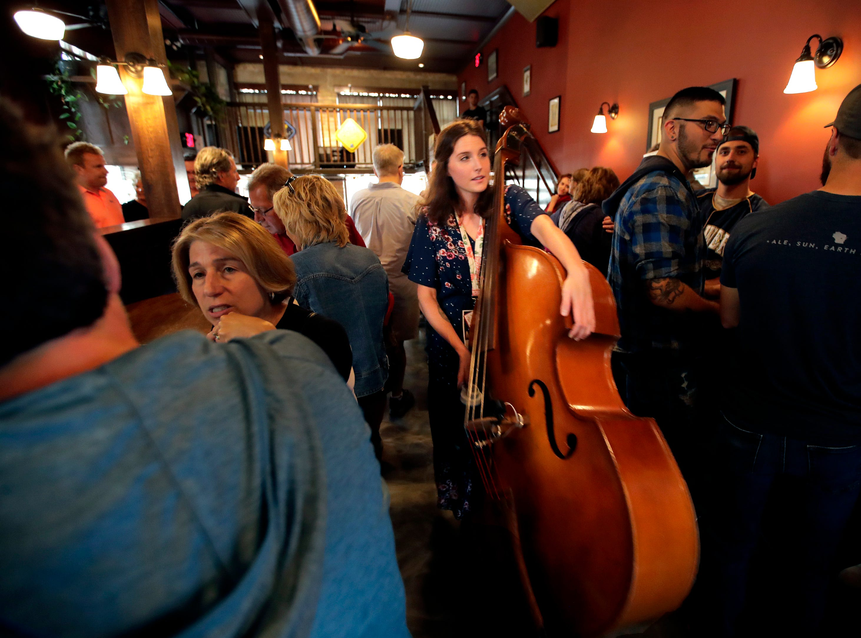 Molly Mathewson, with Last Acre, carries her double bass out of McFleshman's Brewing Co. after their set during the first day of Mile of Music Thursday, Aug. 2, 2018, in Appleton, Wis. Danny Damiani/USA TODAY NETWORK-Wisconsin