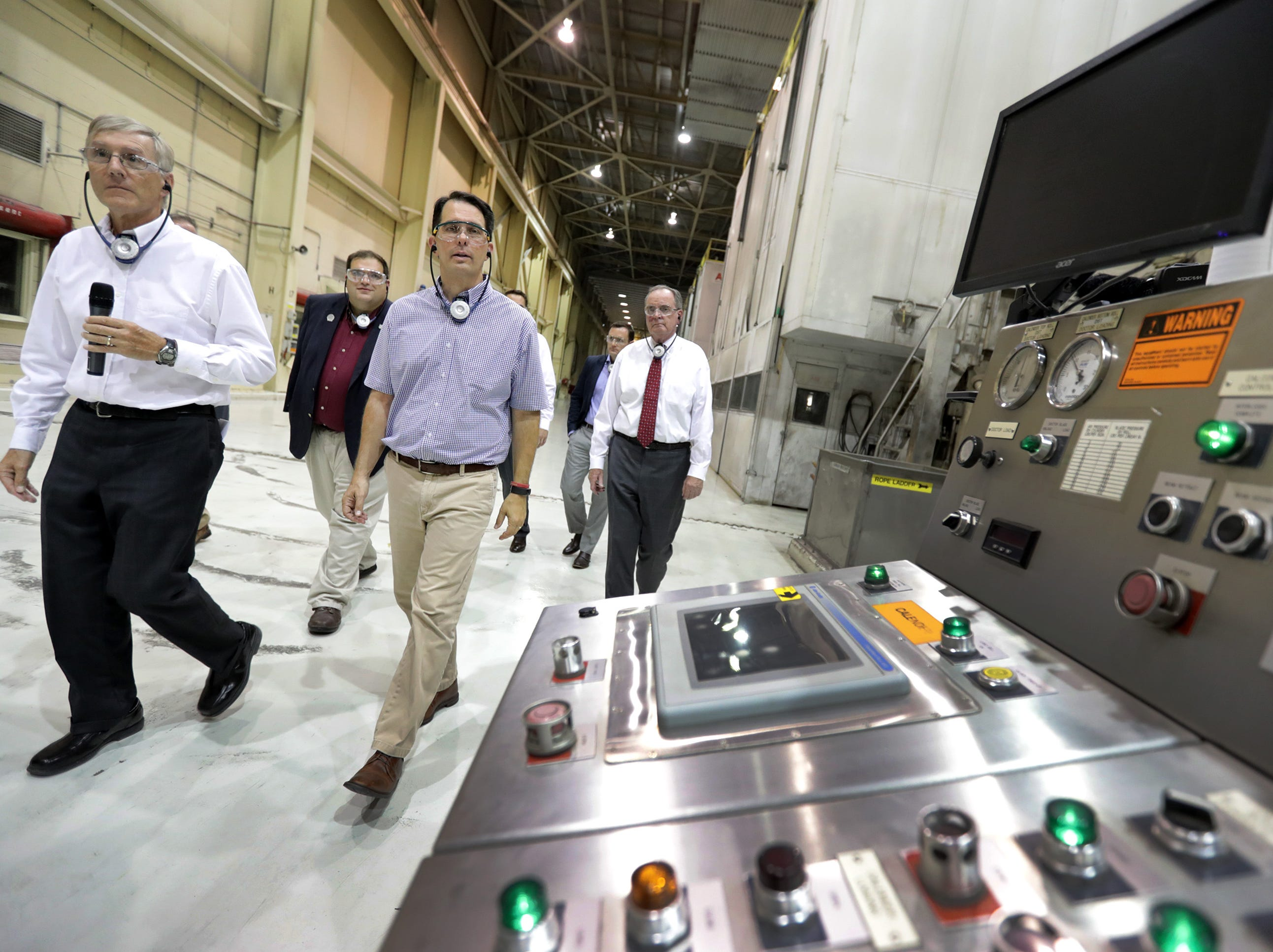 Managing Director Doug Osterberg, left, leads Governor Scott Walker on a plant tour before the announcement of $1.8 million in state tax credits from the Wisconsin Economic Development Corporation to suppoert Midwest Paper Group's effort to modernize the former Appleton Coated Paper Mill on Monday, July 30, 2018 in Combined Locks Wis. Midwest Paper Group has pledged to create 321 jobs and invest $30 million.