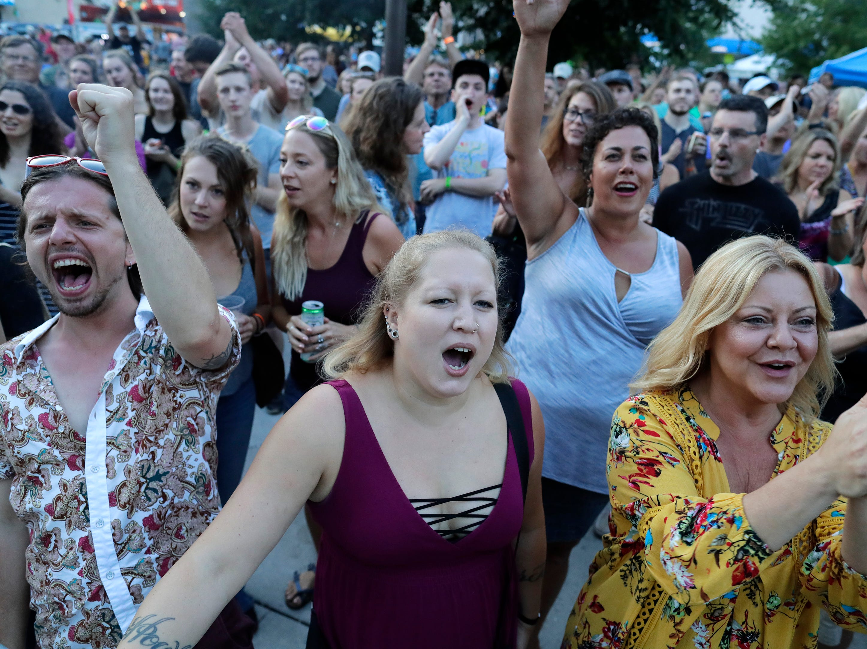 Fans cheer for The JC Brooks Band as they perform at Houdini Plaza during the Mile of Music Friday, August 3, 2018, in Appleton, Wis.  