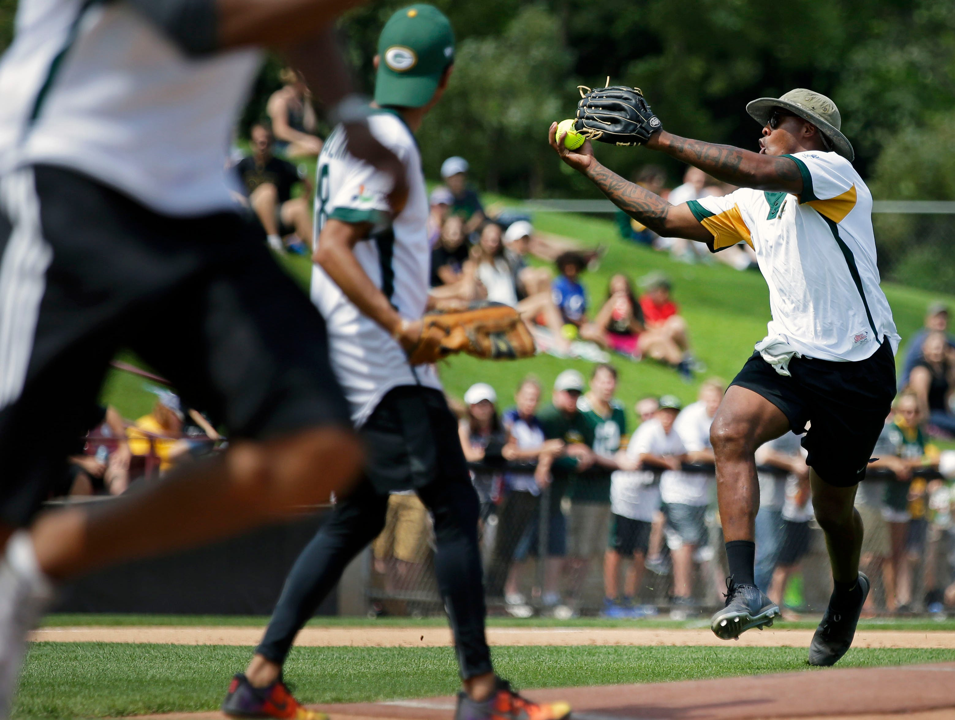 Jermichael Finley tries to control the ball as a runner heads for first during the the charity softball game with Donald Driver and a few of his friends Sunday, August 5, 2018, at Neuroscience Group Field at Fox Cities Stadium in Grand Chute, Wis.