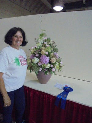 At the third flower show of the Ohio State Fair, Mary Lee Minor stands with her design representative of the Georgian Period in England. This mass design of fresh plant materials was the Judge's choice for distinction.