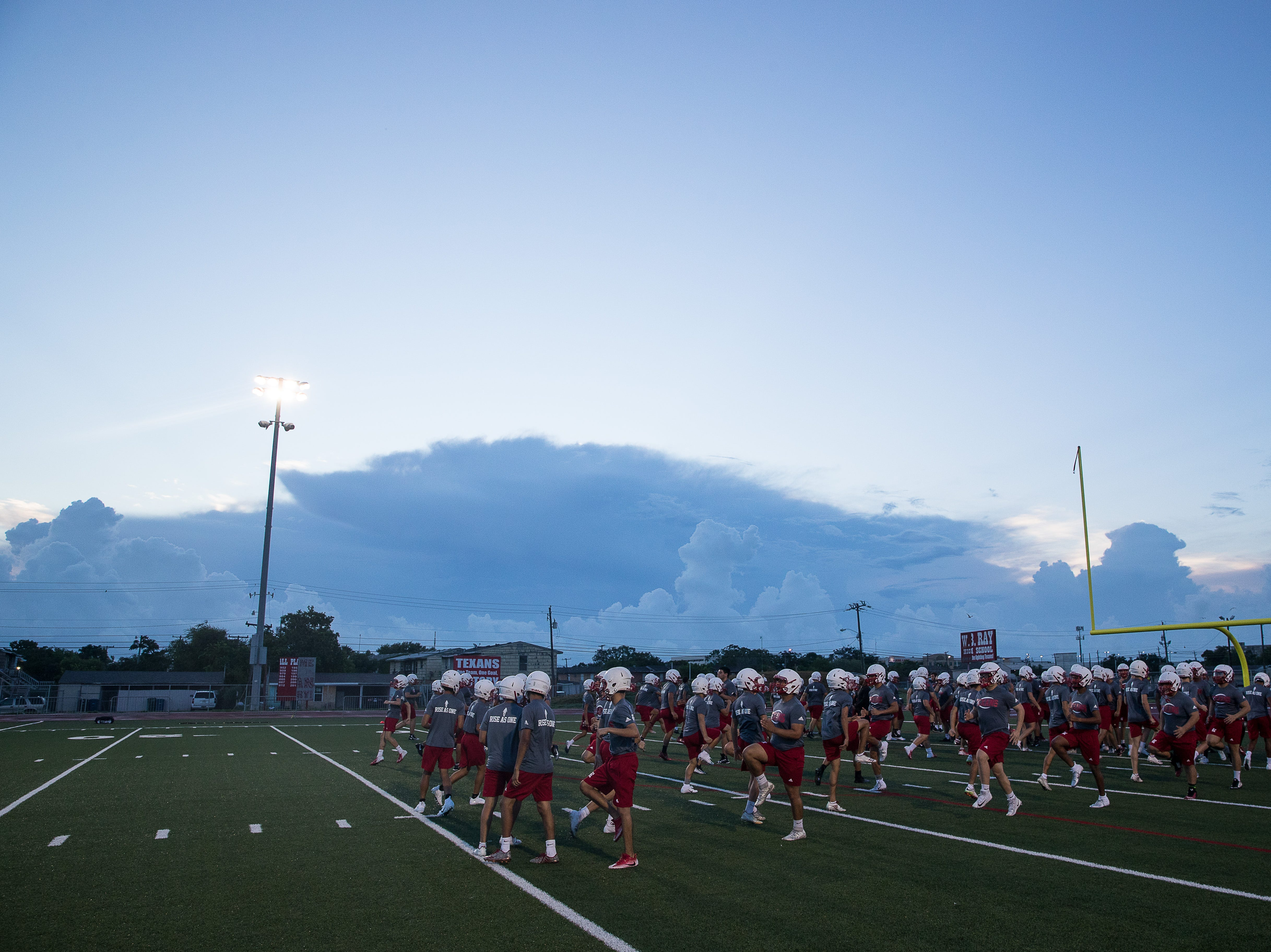 Ray football players warm up on the first day of practice for the 2018 season at Ray High School on Monday, Aug. 6, 2018.